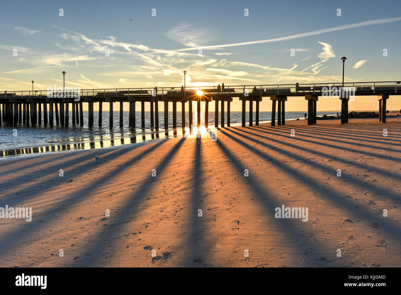 Coney Island Beach at sunset with a vivid, dramatic sky and long shadows. - Stock Image