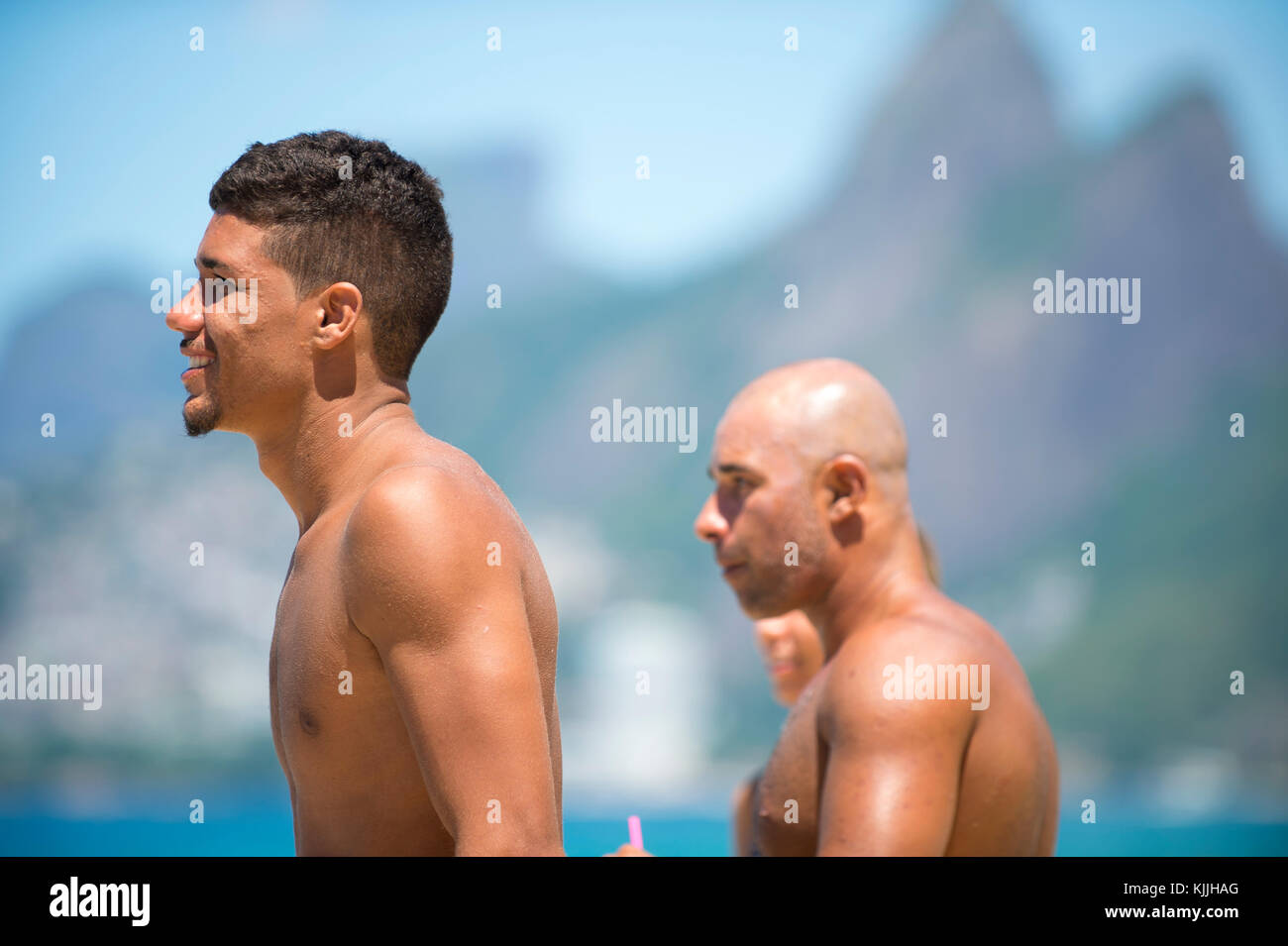 RIO DE JANEIRO - FEBRUARY 9, 2017: Brazilian surfers stand on the beach at Arpoador, the popular surf spot, against - Stock Image