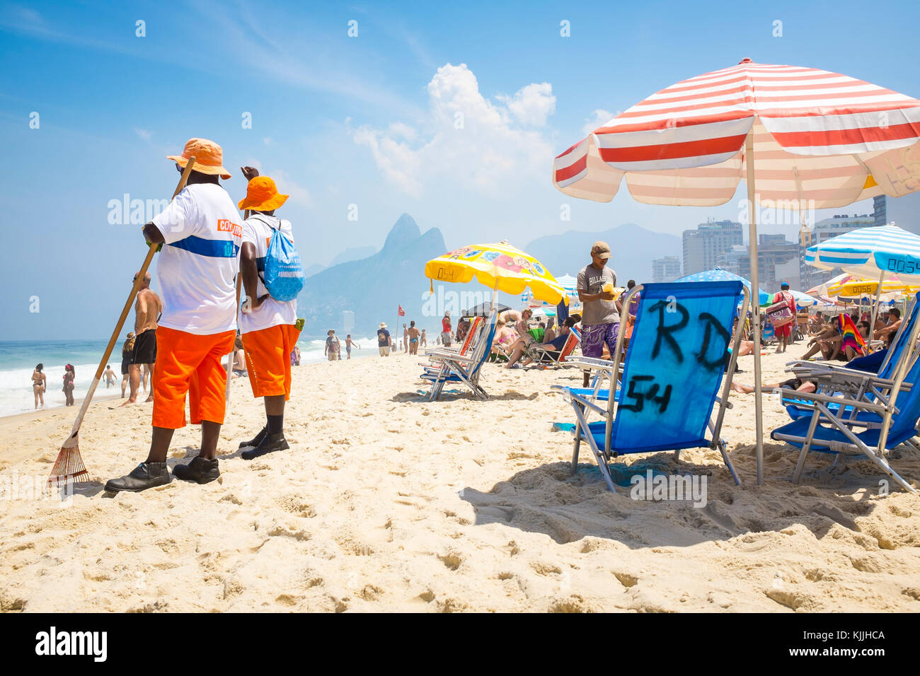 RIO DE JANEIRO - MARCH 06, 2016: Beach cleaners on busy Ipanema Beach with parasols and chairs with two brothers - Stock Image