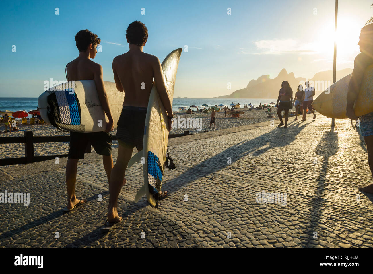 RIO DE JANEIRO - MARCH 24, 2017: Sunset silhouettes of two young surfers walking with surfboards at Arpoador with - Stock Image
