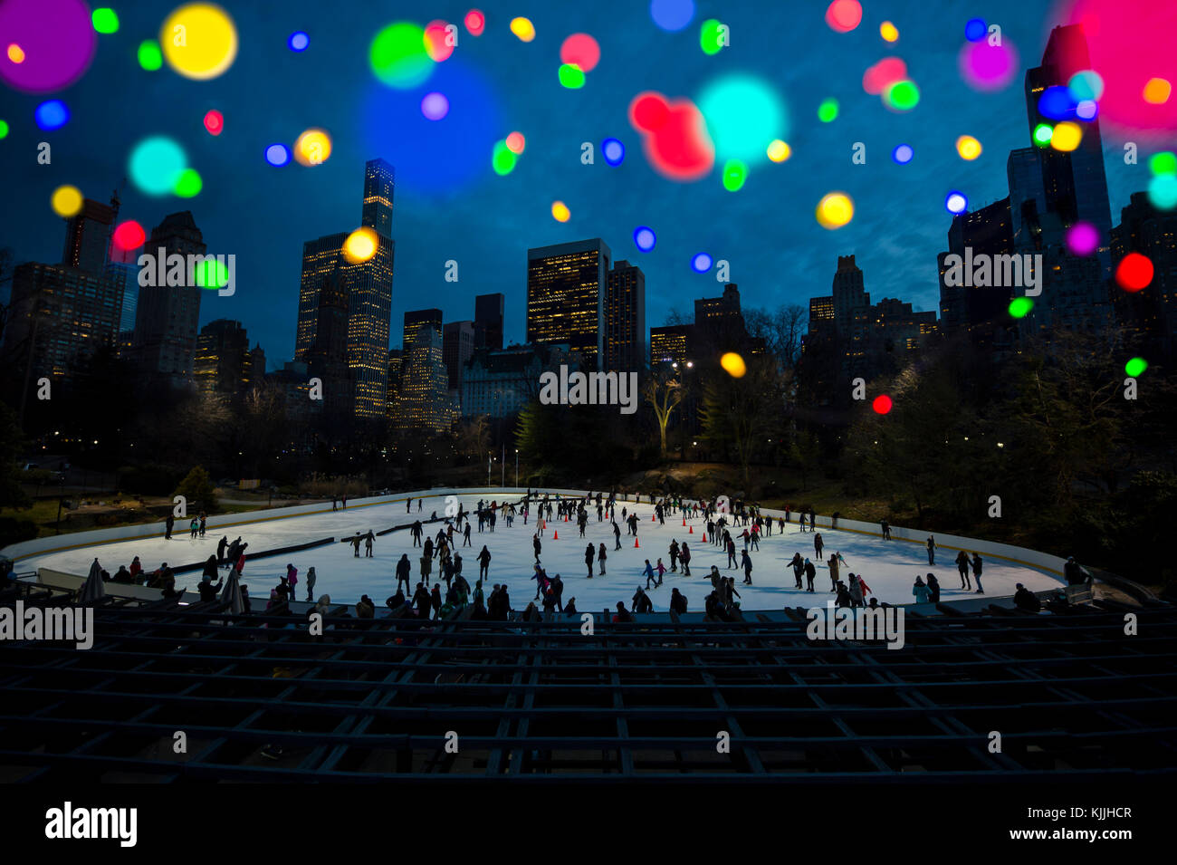 Scenic city skyline night view with ice skating rink at dusk with abstract defocus bokeh christmas lights Stock Photo