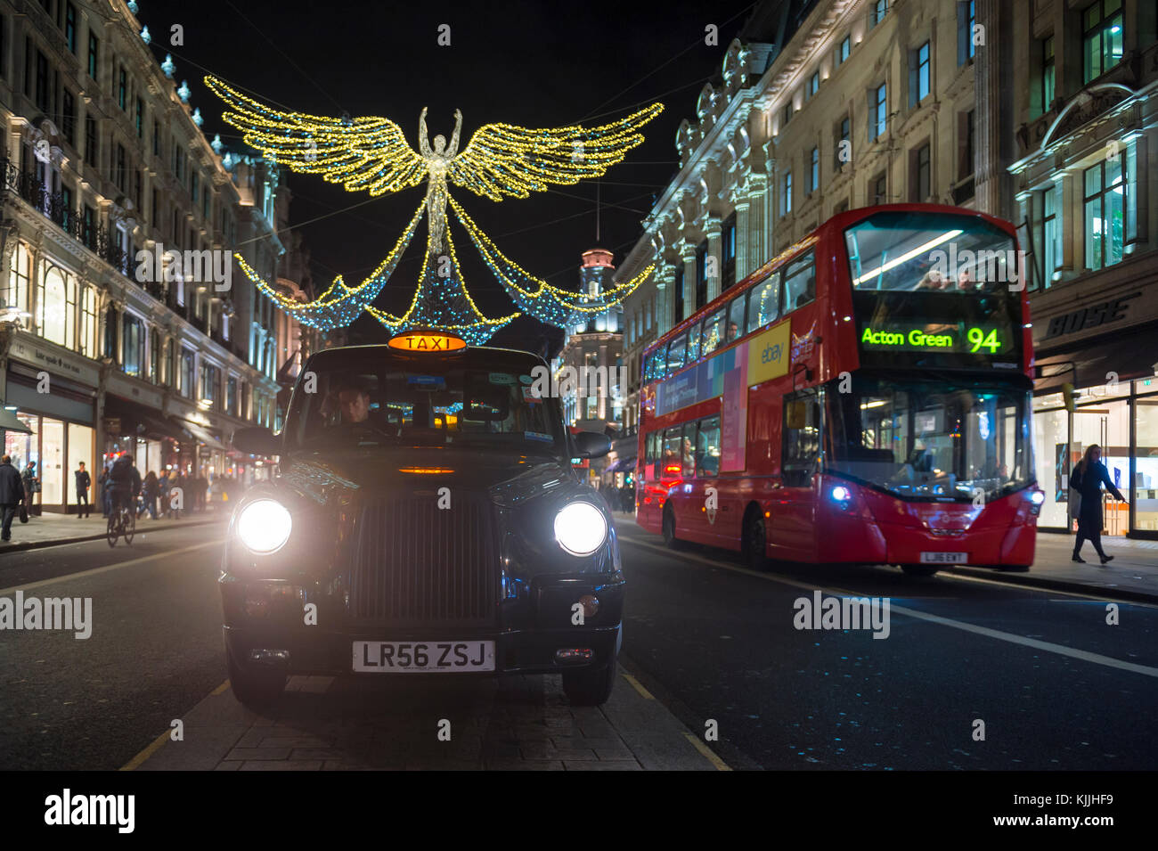 LONDON - NOVEMBER 21, 2017: Double decker buses and black cabs jam the streets under twinkling Christmas angels - Stock Image