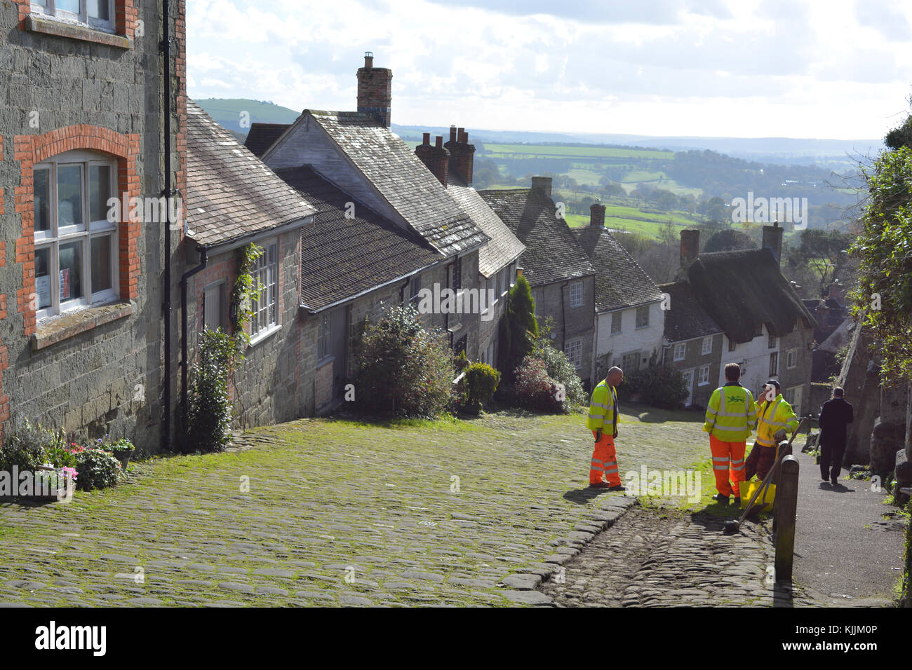 Three workmen discussing clearing the grass from the cobblestones of Shaftesbury Gold Hill, Dorset, England - Stock Image