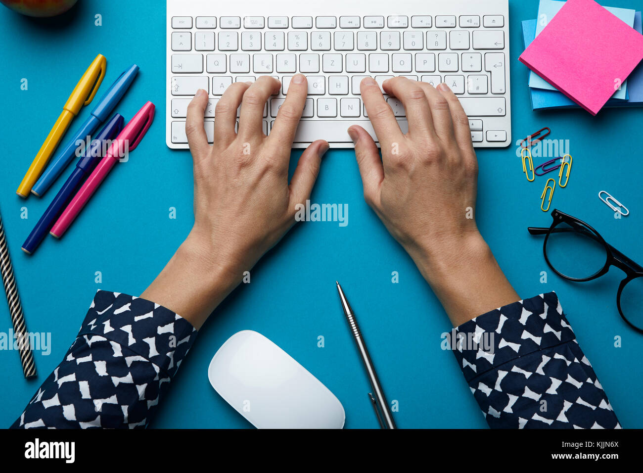 Top view of woman using computer keyboard on desk - Stock Image