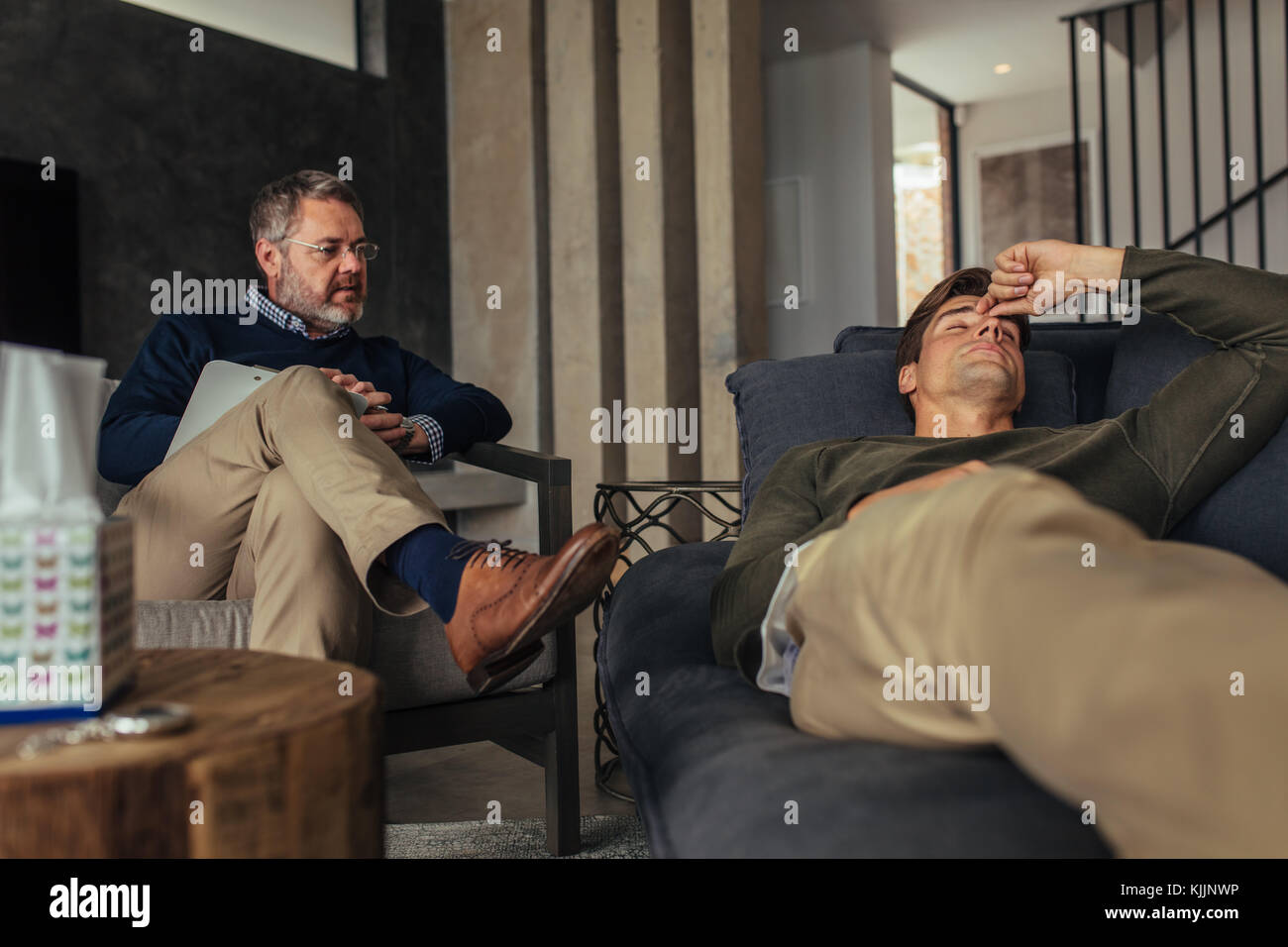 Stressed man listening psychologist's analysis. Male patient lying on sofa during psychotherapy session. Stock Photo