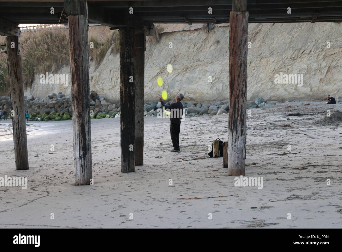 Man juggles yellow frisbees on the beach, Capitola, CA. - Stock Image