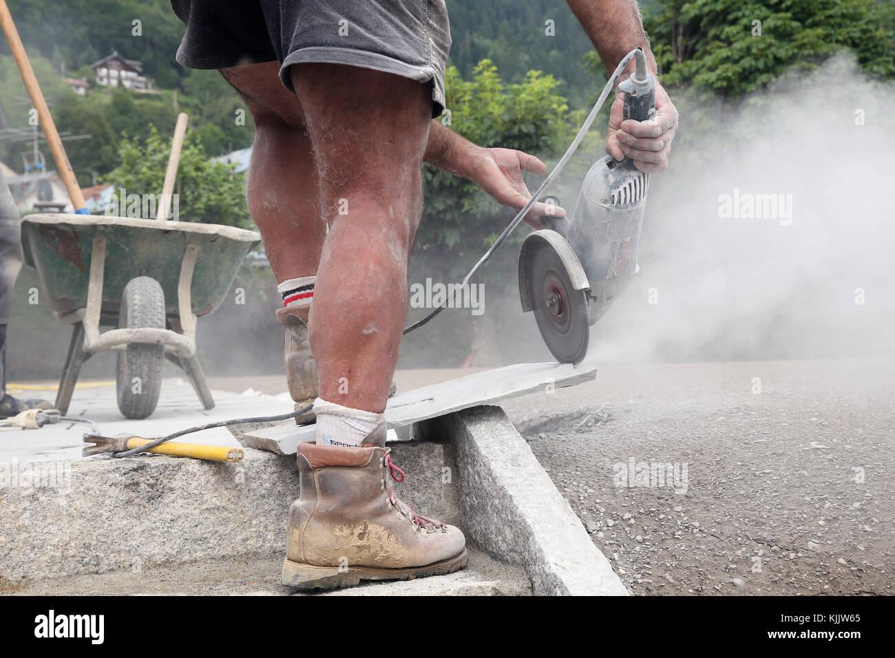 Worker  cuts stone tiles with a saw. France. Stock Photo