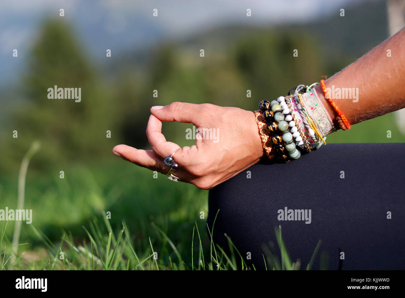 Woman sitting with her legs crossed and hand resting on knee. Mudra posture. Close-up.  France. - Stock Image