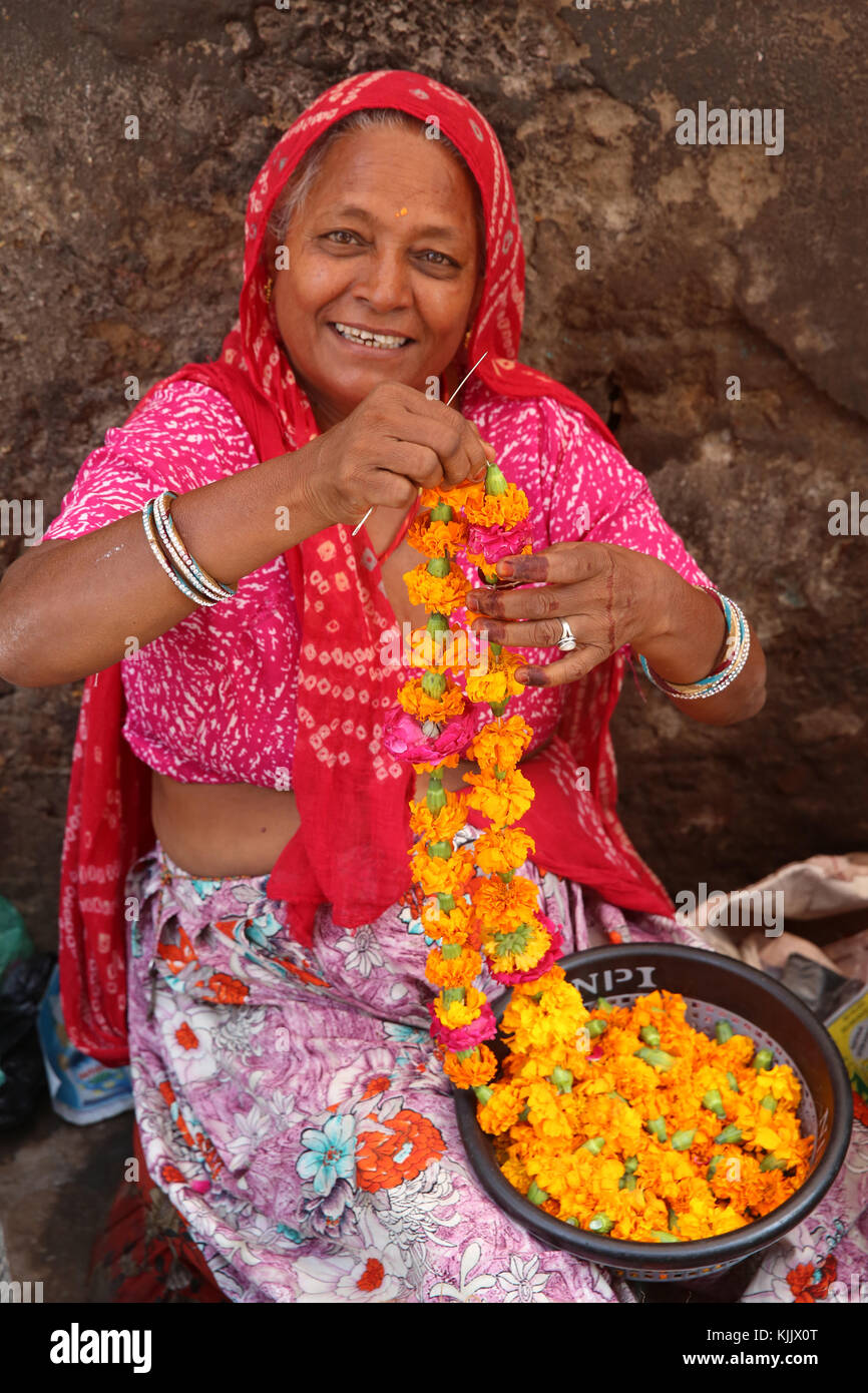 Indian woman making garlands in Ajmer, India. - Stock Image