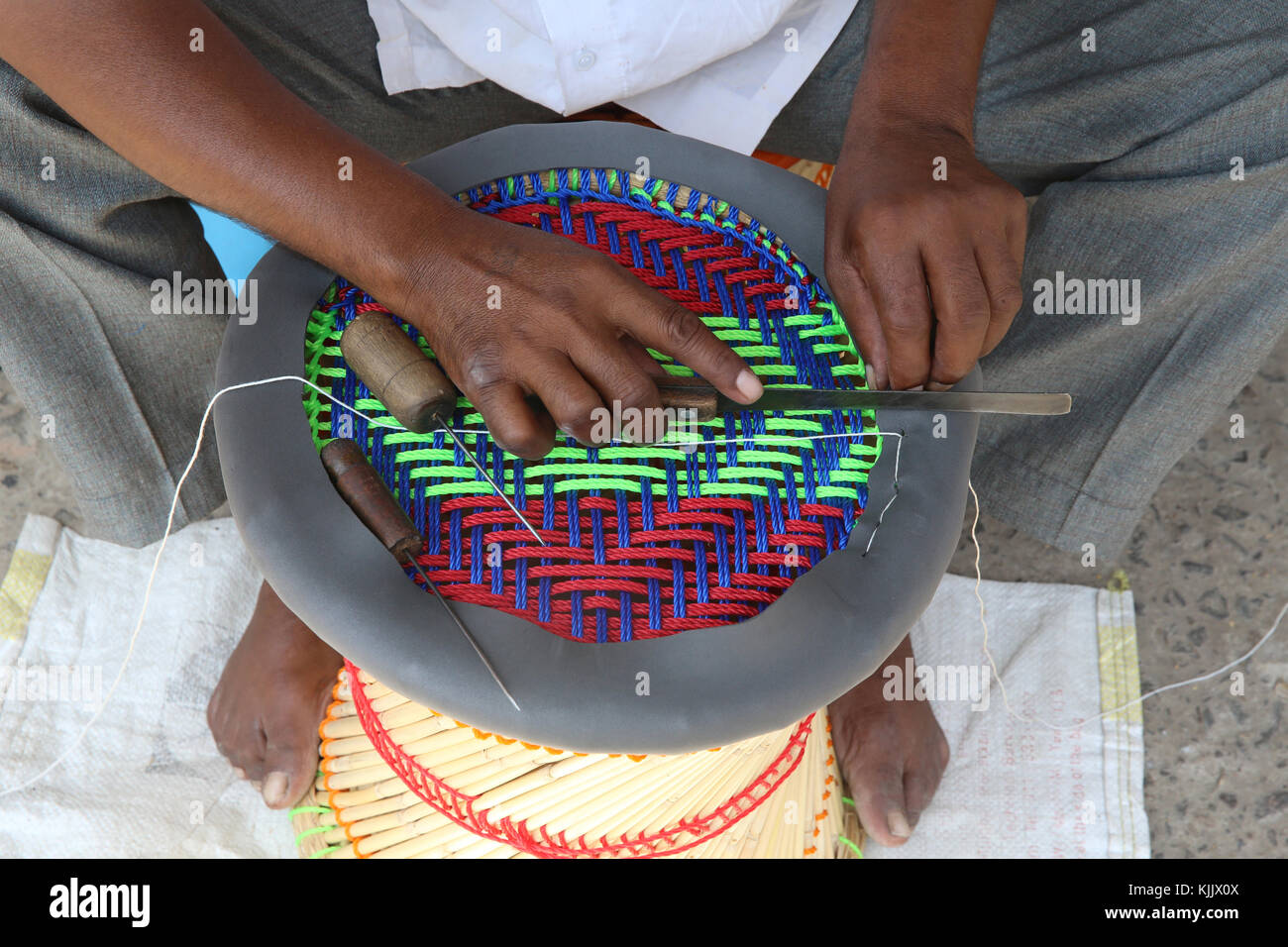 Rajasthan craftsman making a 'muddha', small stool made of reeds and colored string. India. - Stock Image