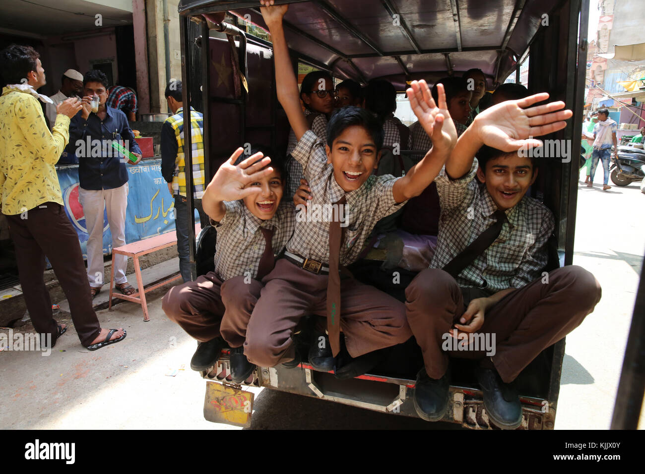 Ajmer schoolboys waving from a vehicle. India. - Stock Image