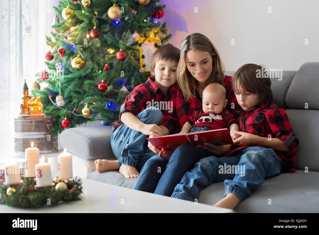 Happy family portrait on Christmas, mother, reading a book to her three children sitting on couch at home, chritmas - Stock Image