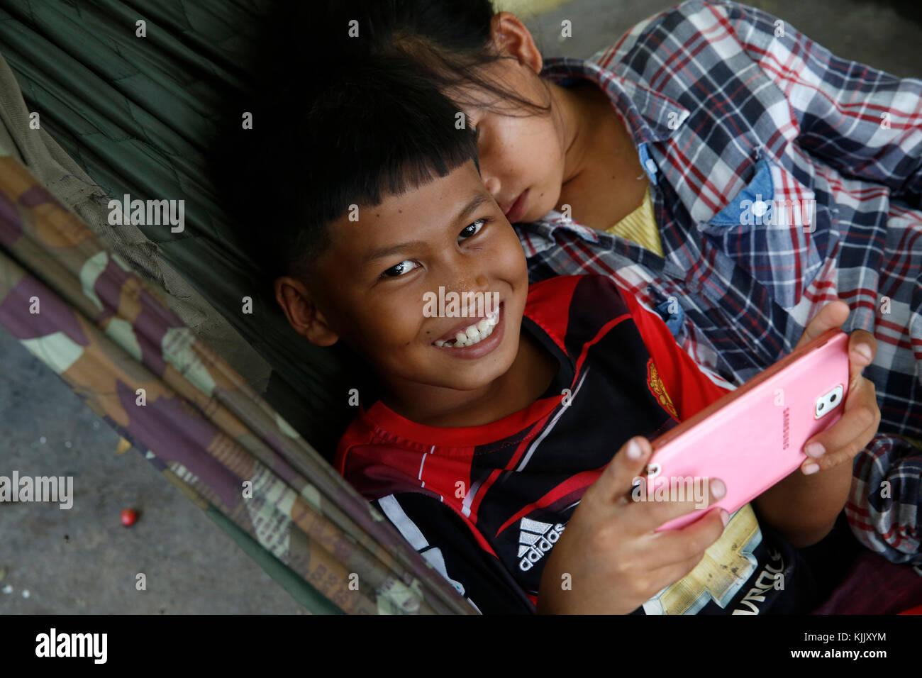 Children playing in a hammock. Battambang.  Cambodia. - Stock Image