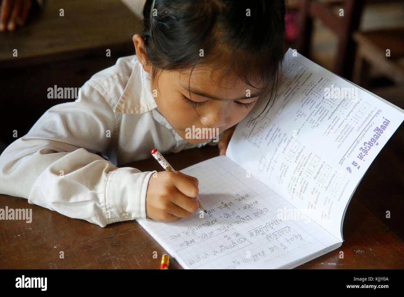 Cambodian schoolgirl writing in an exercise book. Battambang.  Cambodia. - Stock Image