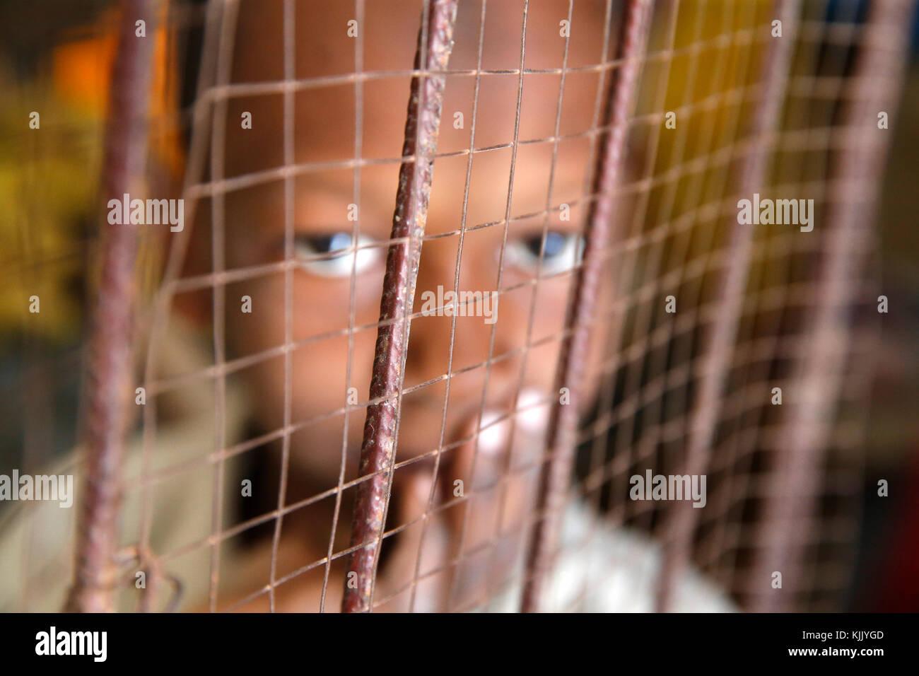 Dakar boy behind a wire mesh. Senegal. - Stock Image