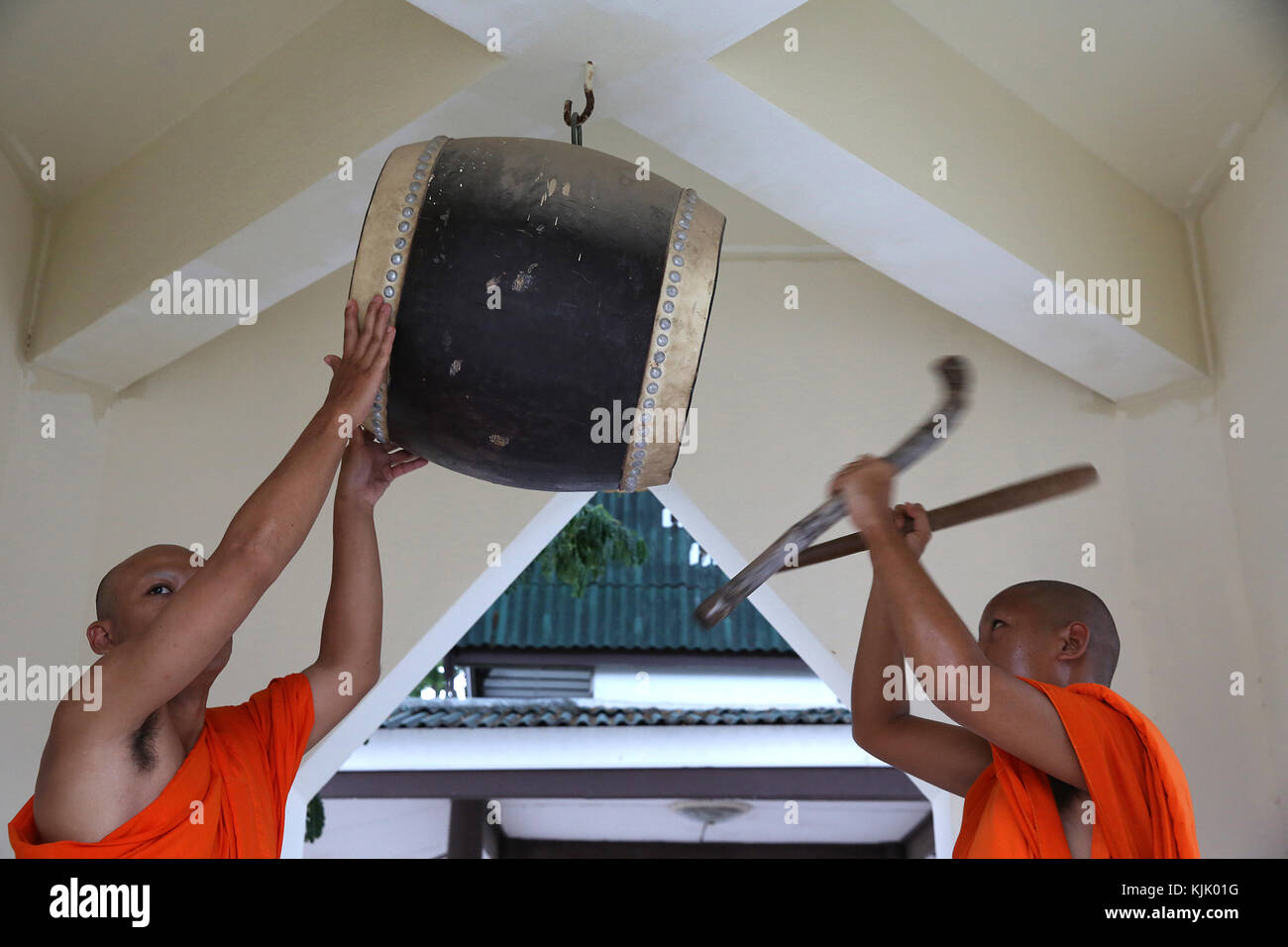 Monks beating drum in a Hua Hin temple. Thailand. - Stock Image