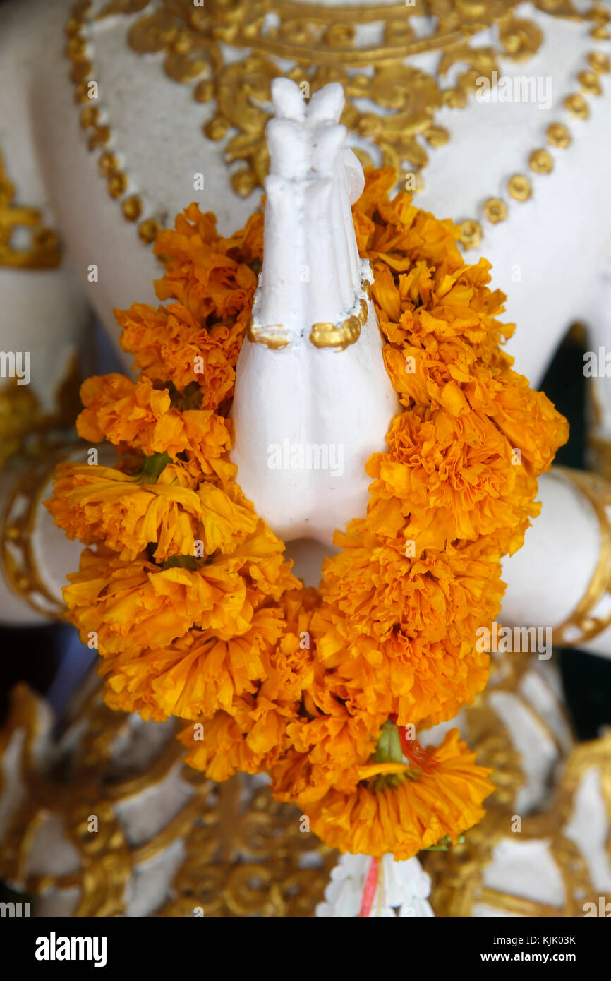Detail of a garlanded statue in Wat Inthakin, Chiang Mai. Thailand. - Stock Image