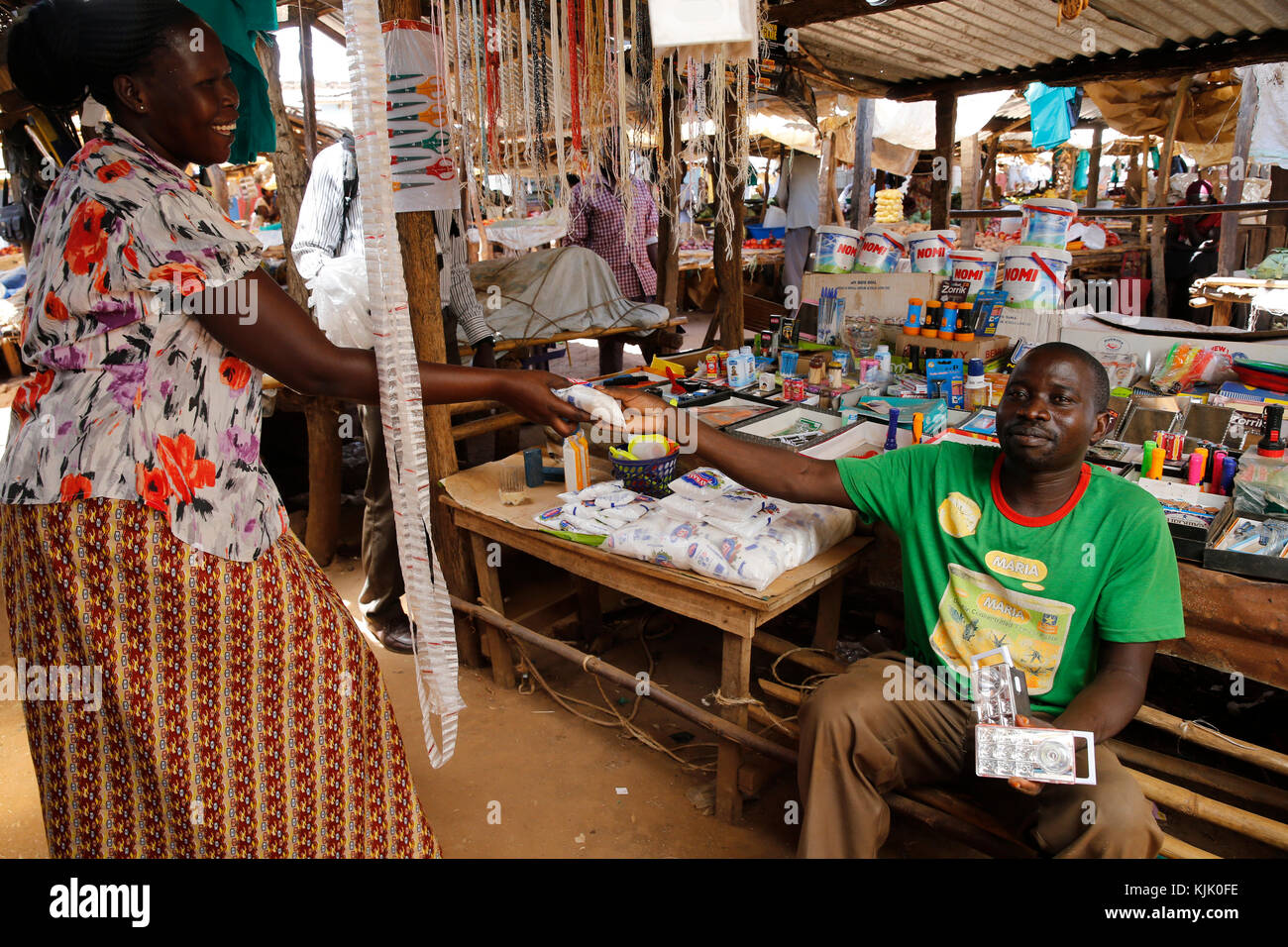Michael Nakuni runs a stall at Bweyale market. He received 4 loans from Uganda Microfinance Foundation. Uganda - Stock Image