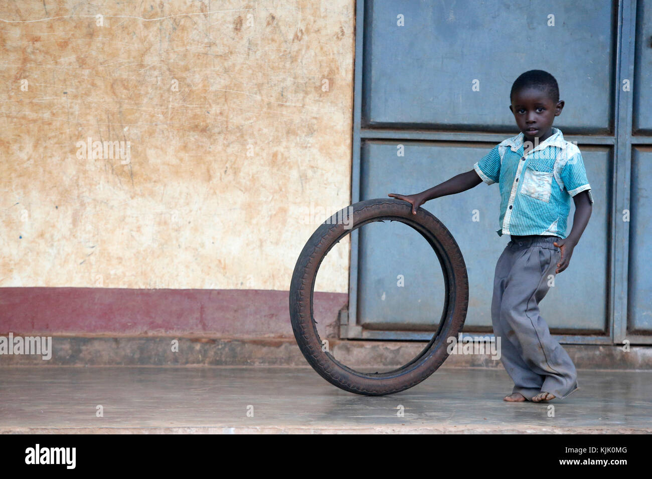 Ugandan child playing with a tyre. Uganda - Stock Image