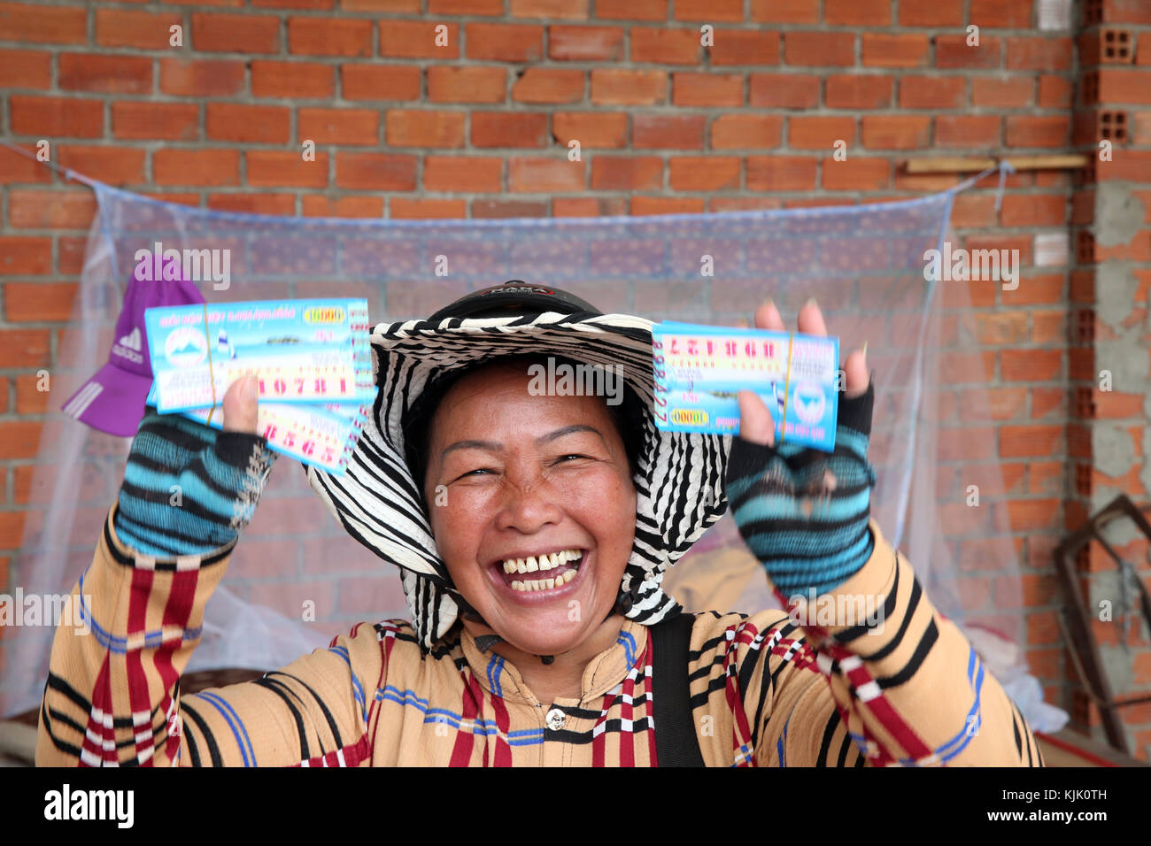 Smiling woman selling lottery tickets.  Thay Ninh. Vietnam. - Stock Image