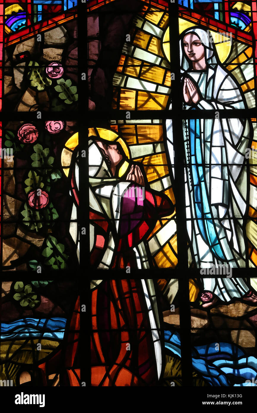 Dalat cathedral.  Stained glass window. Our Lady of Lourdes: An image depicting Mary appearing on the grotto, in Stock Photo