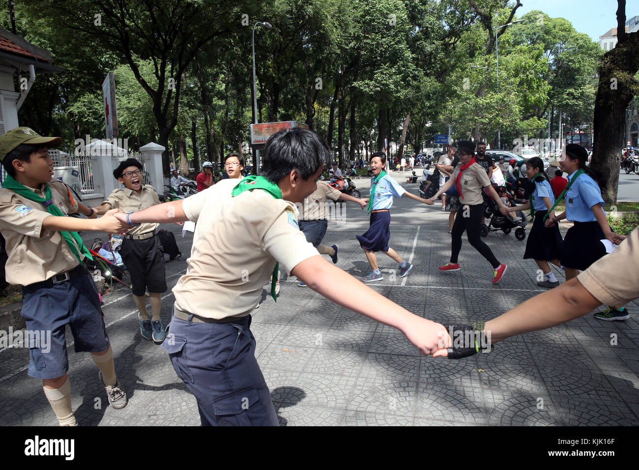 Vietnamese scout troup dancing in the street.  Ho Chi Minh City.  Vietnam. - Stock Image