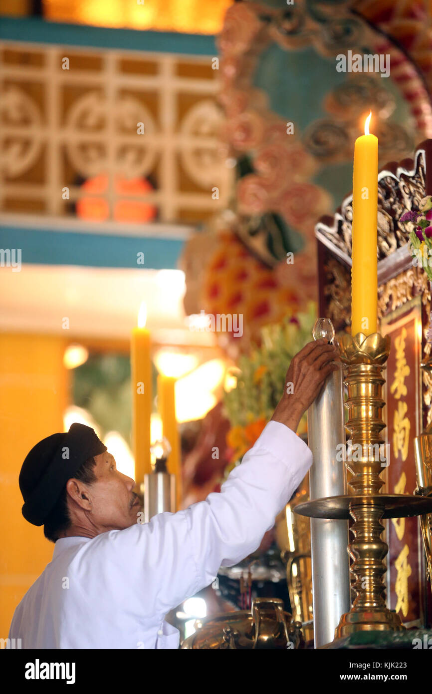 Cao Dai Holy See Temple.  Priest lighting candle on altar for  12 o'clock ritual.  Thay Ninh. Vietnam. Stock Photo