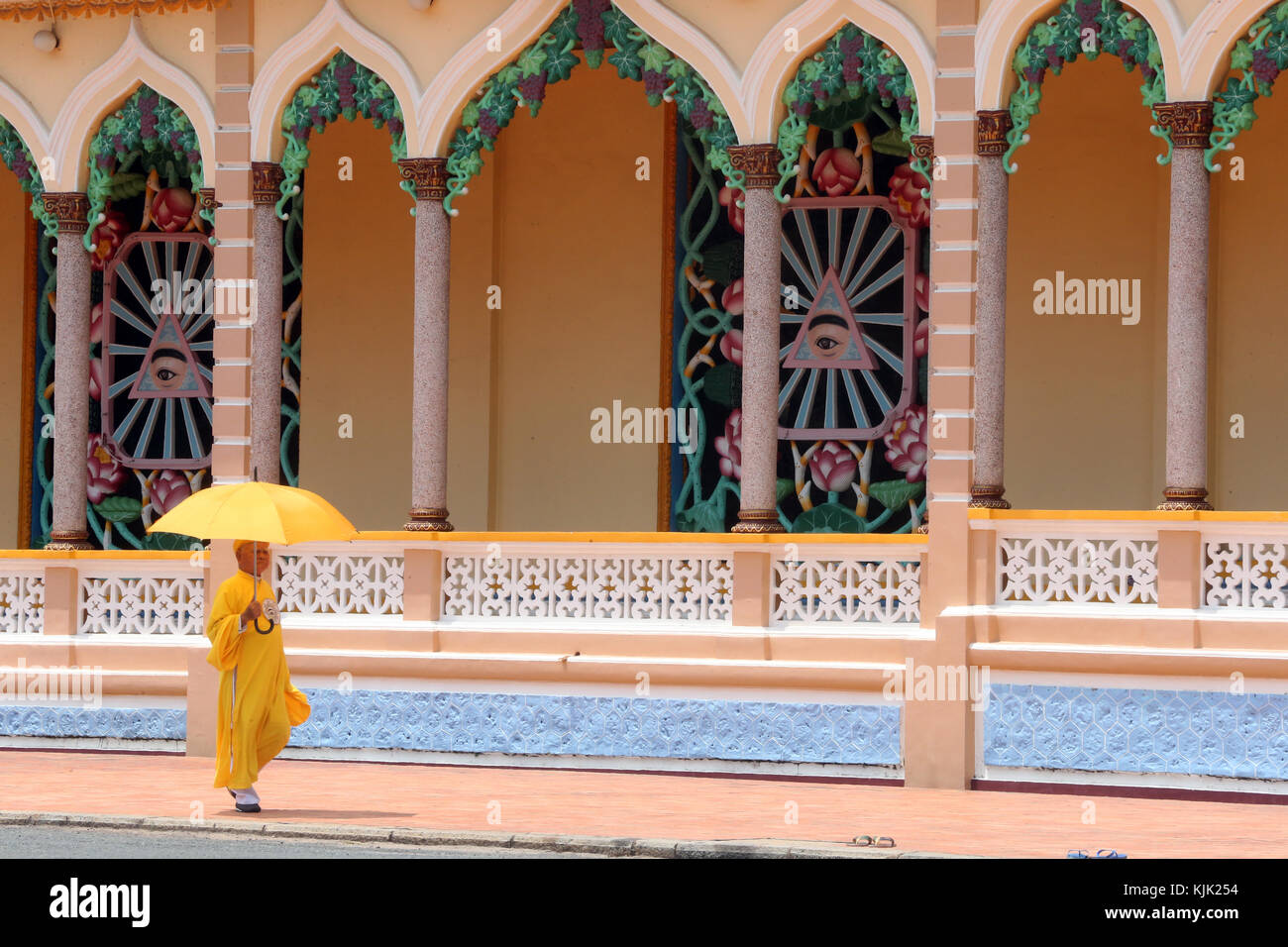 Cao Dai Holy See Temple.  Priest with yellow umbrella.  Thay Ninh. Vietnam. - Stock Image