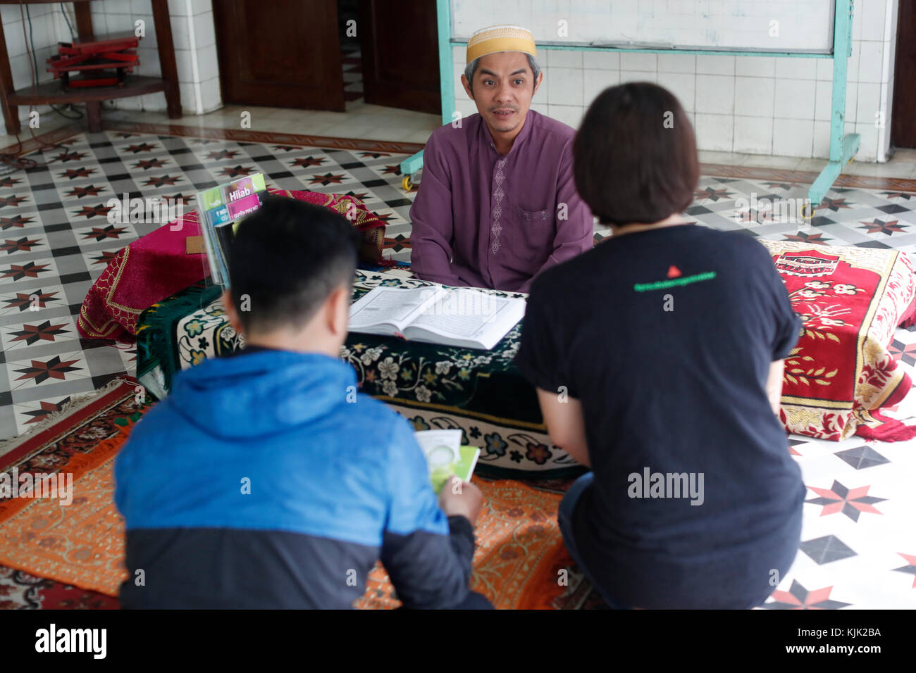 Saigon Central Mosque. Muslim man giving brochures to a young couple.  Ho Chi Minh City.  Vietnam. - Stock Image