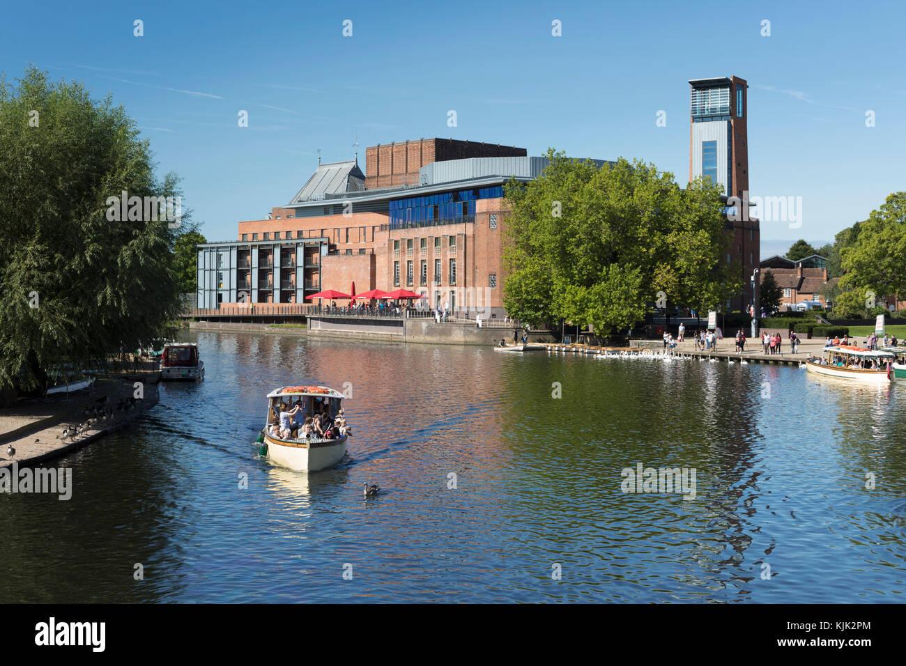 Tour boat cruising past the Royal Shakespeare Theatre on the River Avon, Stratford-upon-Avon, Warwickshire, England, - Stock Image