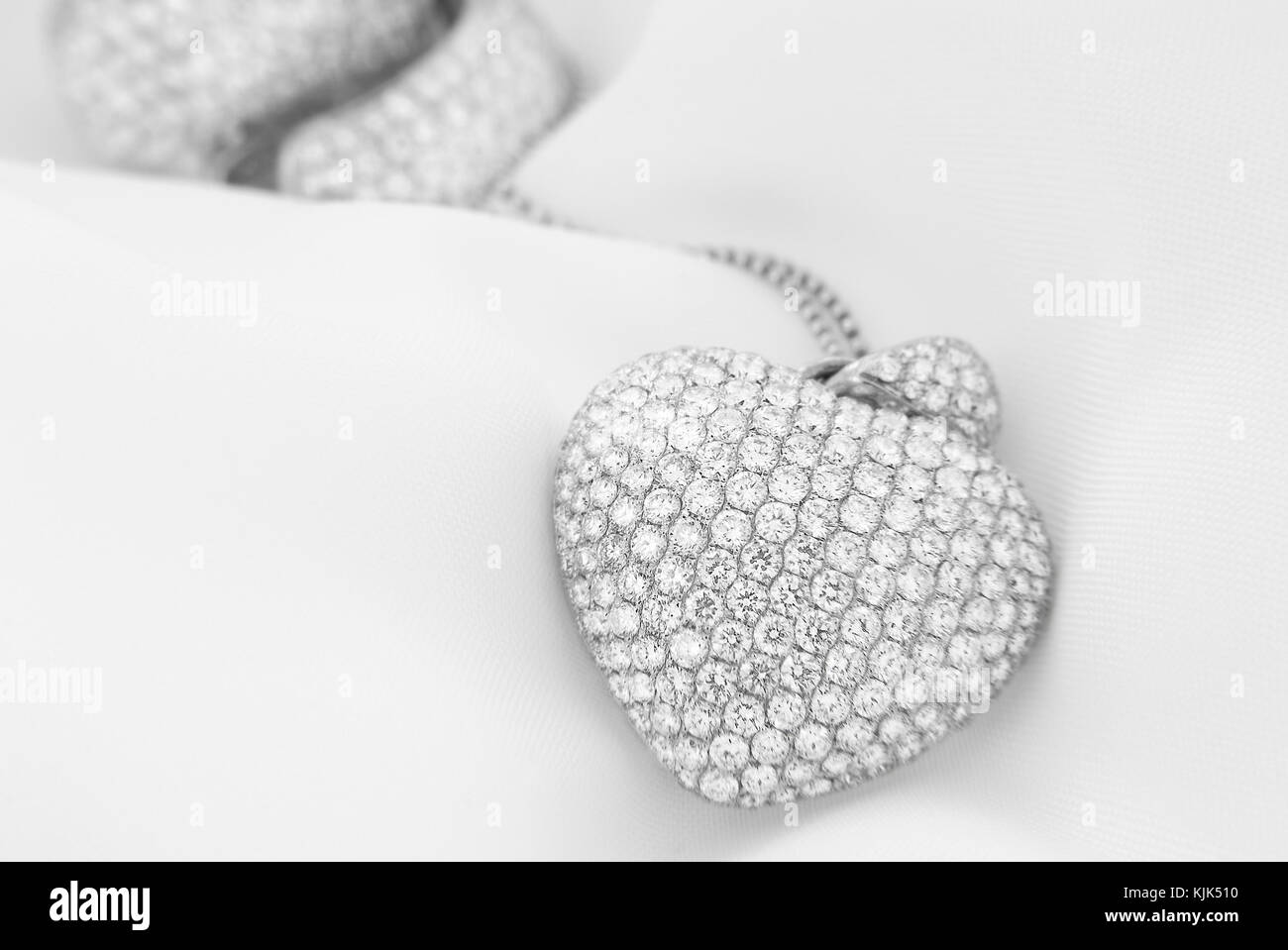 White gold earrings and heart shaped necklace with white diamonds on soft blurred background - Stock Image