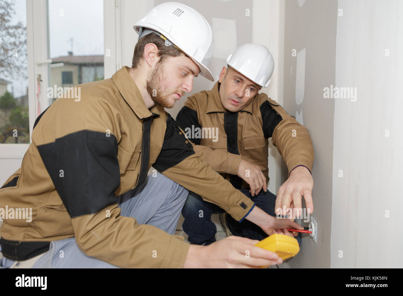 builders using a yellow multimeter to calibrate house Stock Photo