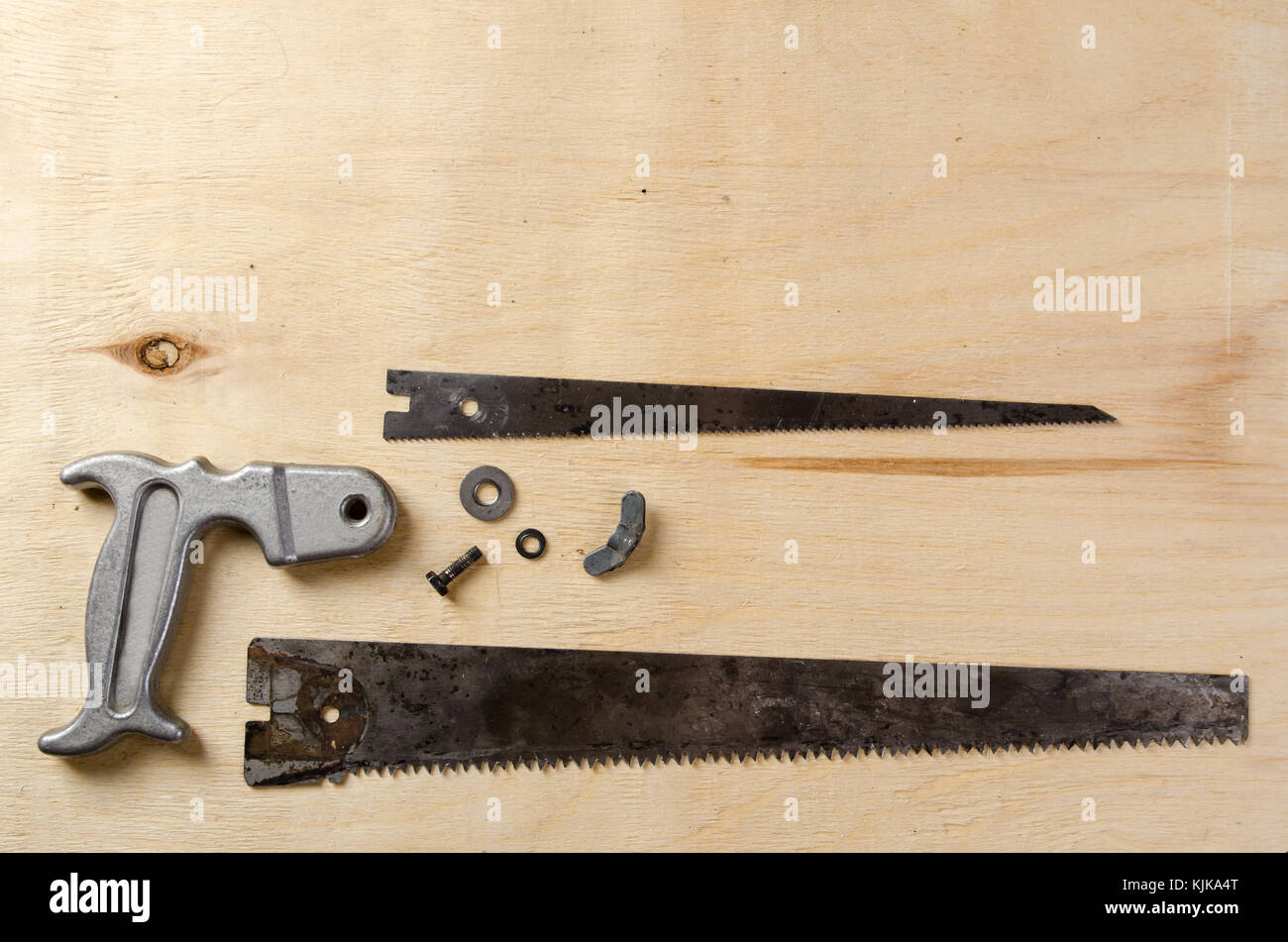 disassemble hand saw lying on a sheet of plywood. flat view. - Stock Image