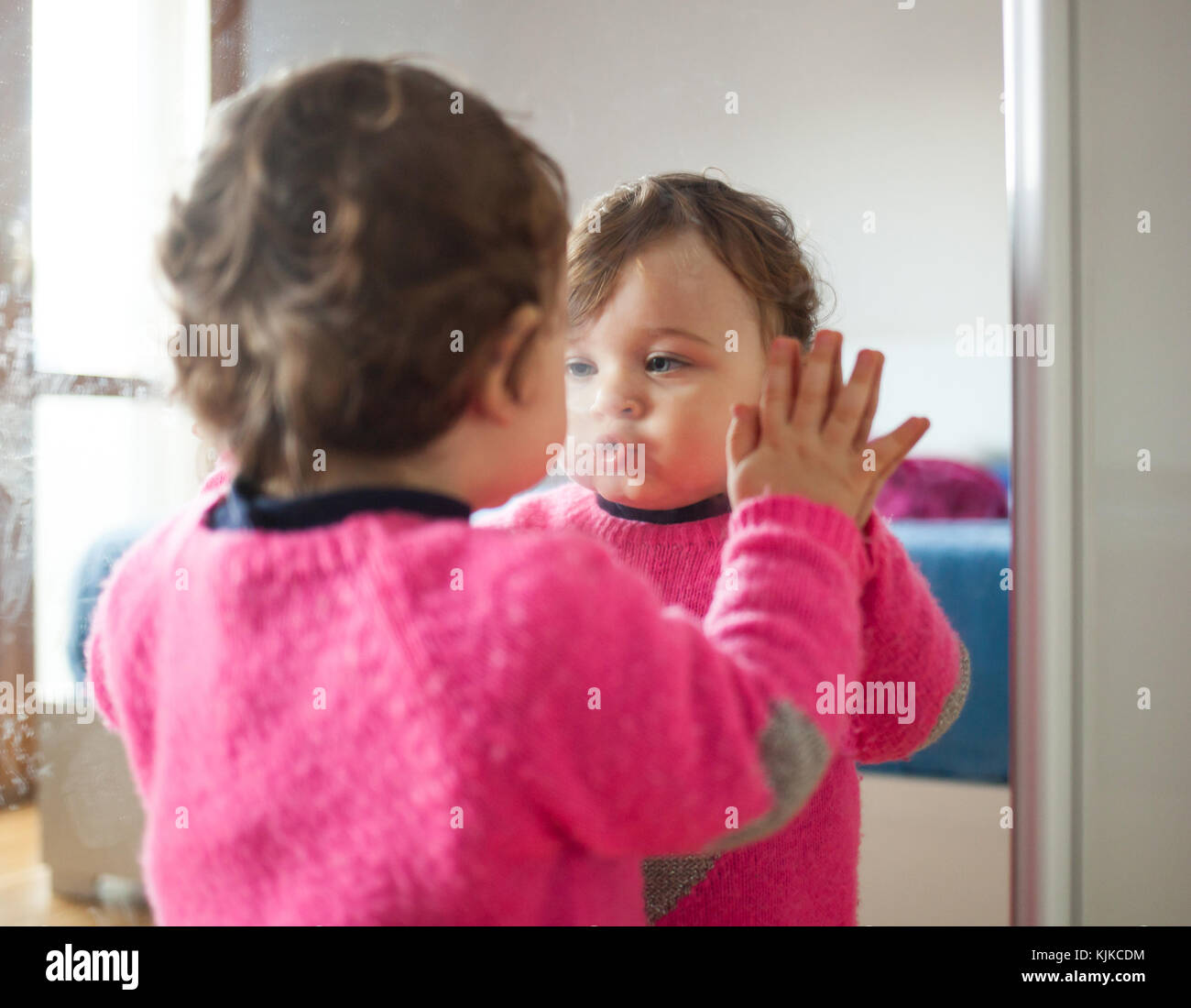 Toddler baby girl playing with mirror in the bedroom. - Stock Image