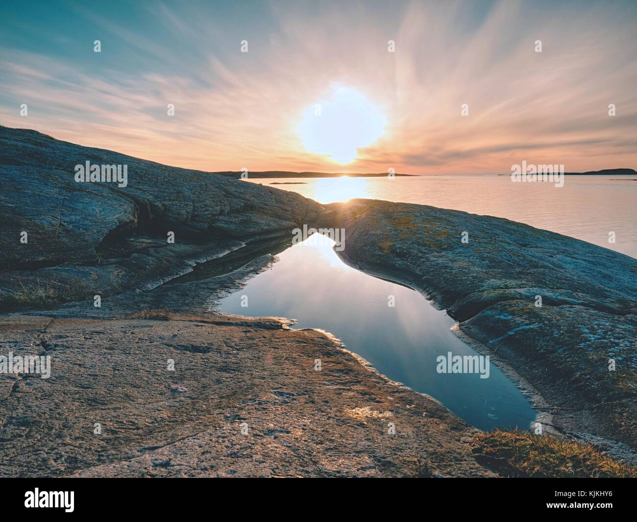 Concept of seascape sunset or sunrise background with rich reflection in water pool. The sun is hanging at horizon - Stock Image