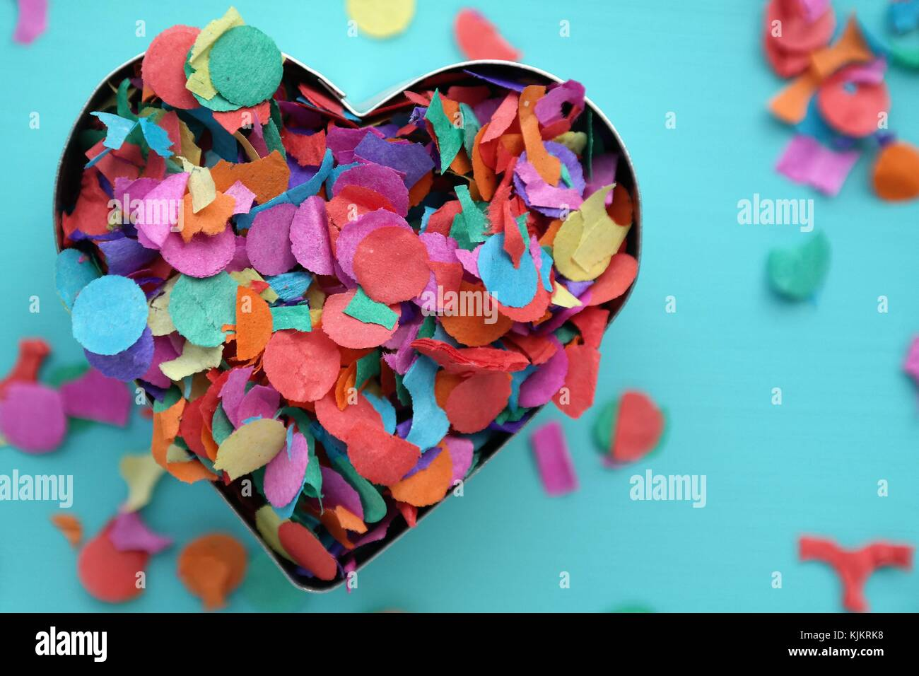 valentine, heart with colorful confetti on blue background. Carnival, creative concept with copy space - Stock Image
