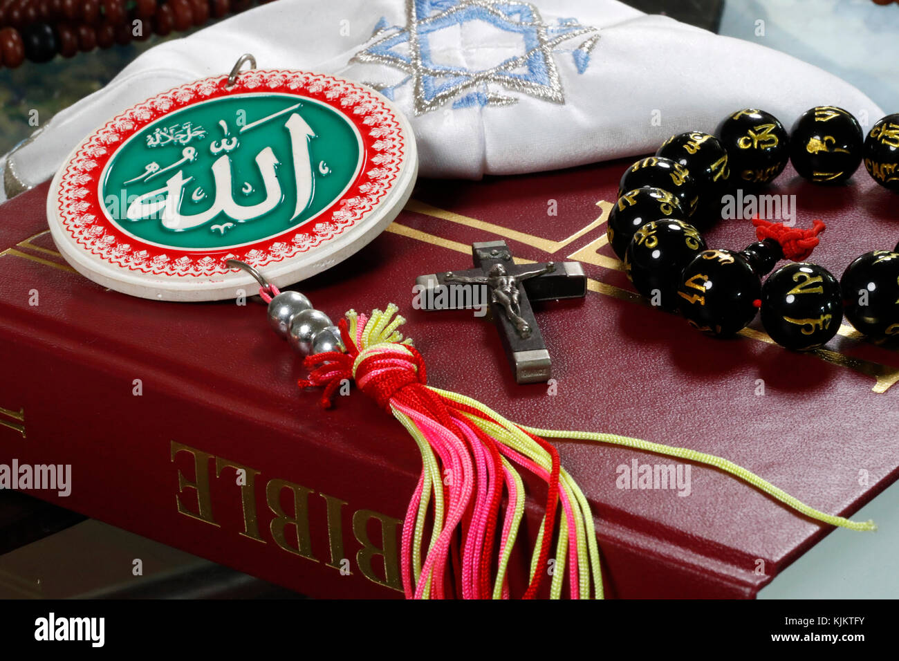 Christianity, buddhism,  Islam and Judaism. Interfaith symbols : bible, cucifix, Kippah, Allah monogram  and mala. - Stock Image