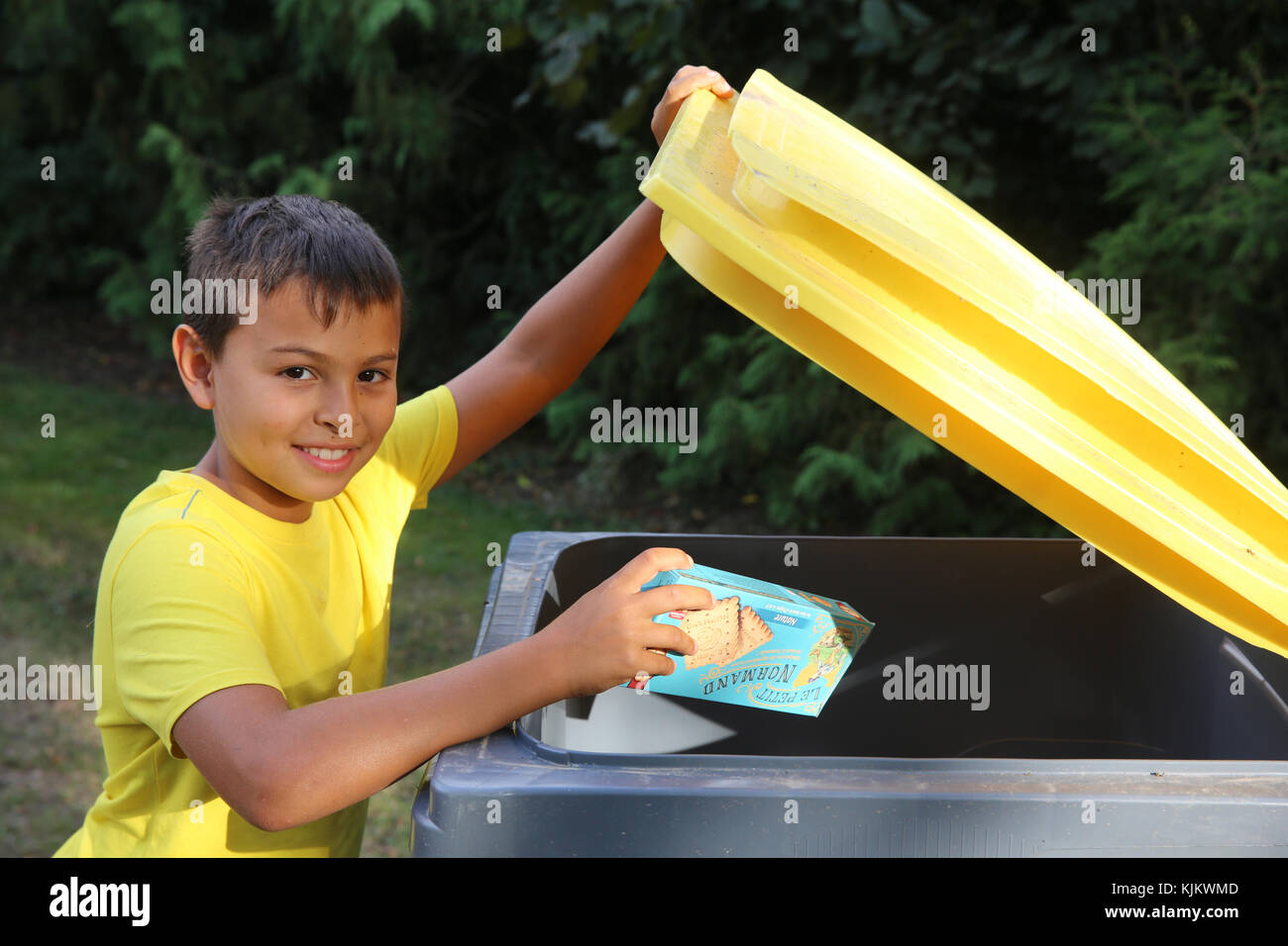 Boy throwing a box in a recycling trash can. France. Stock Photo