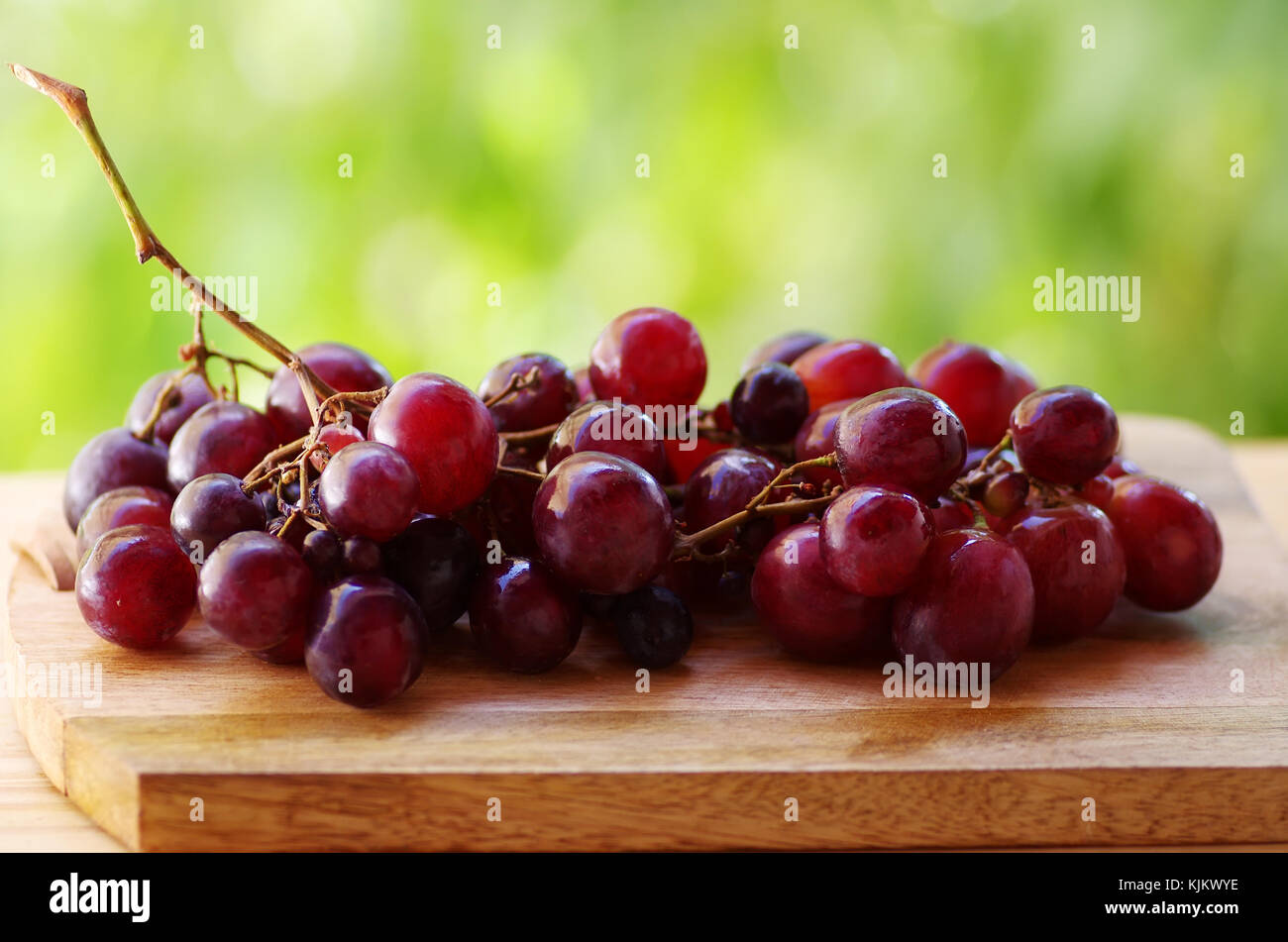 Bunch of red grapes on table, green background Stock Photo