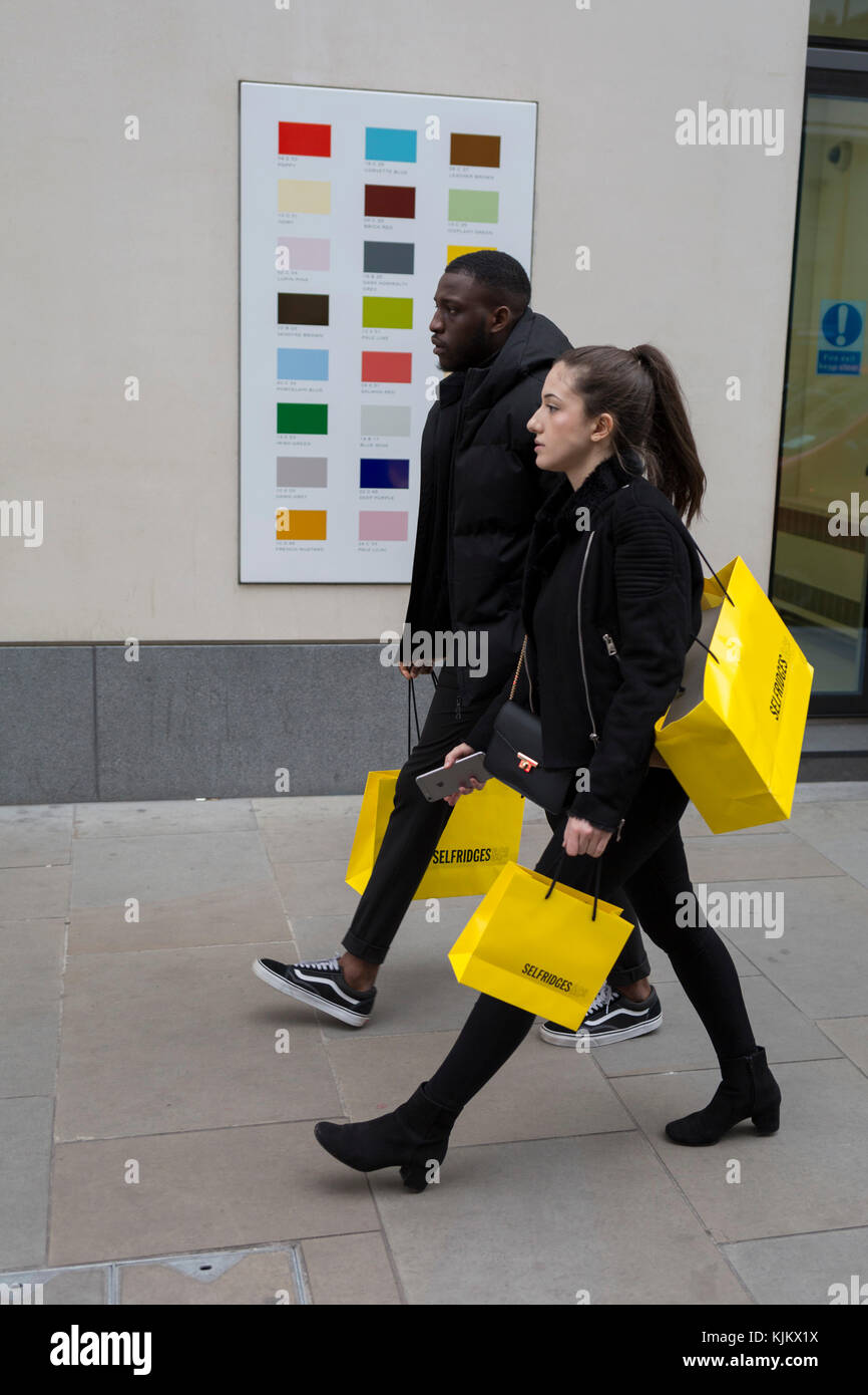 Shoppers carrying a yellow bag from Selfridges department store walks past a colour swatch on the wall of a central - Stock Image