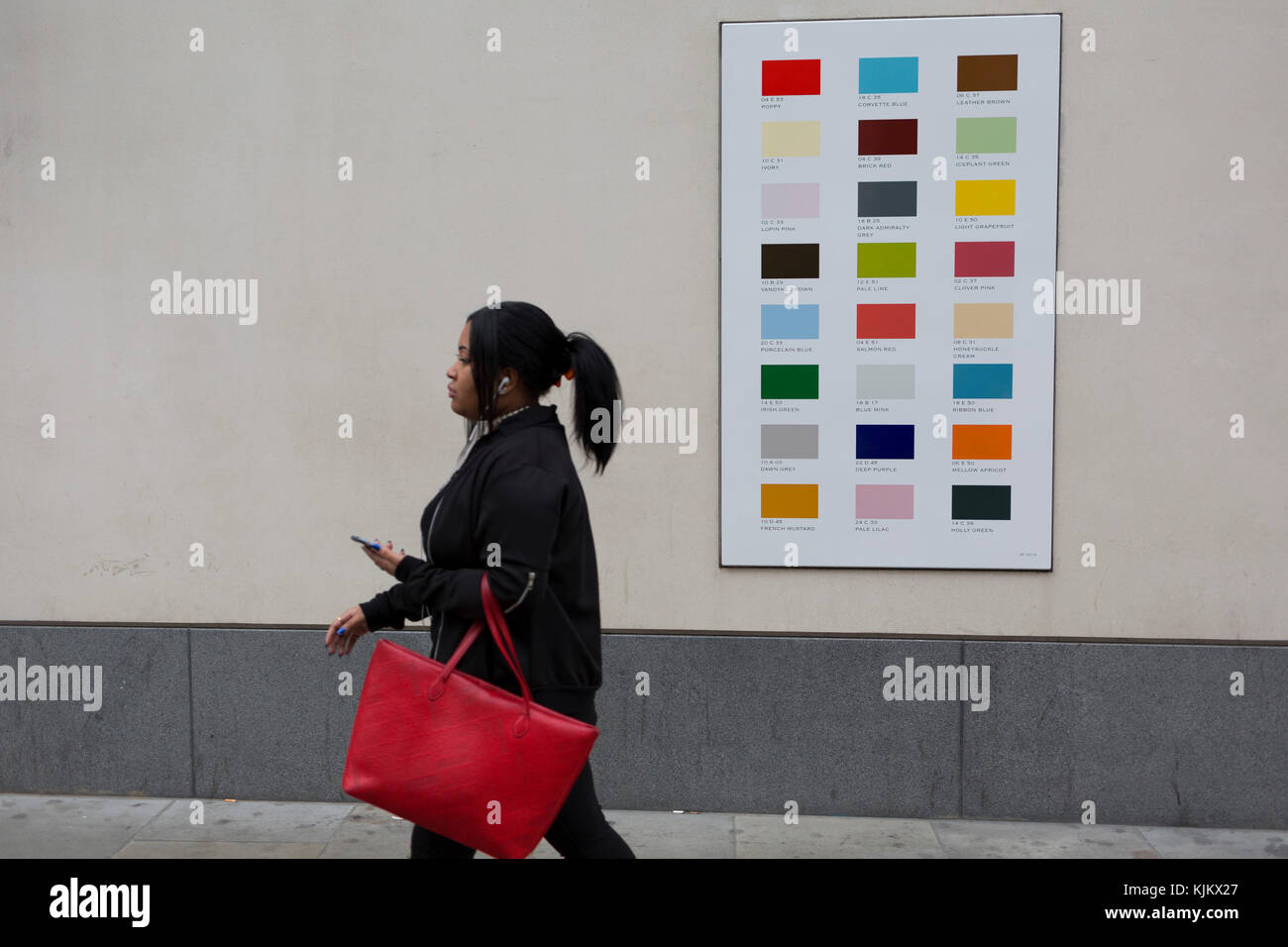 A woman carrying a red bag walks past a colour swatch on the wall of a central London business, on 22nd November - Stock Image