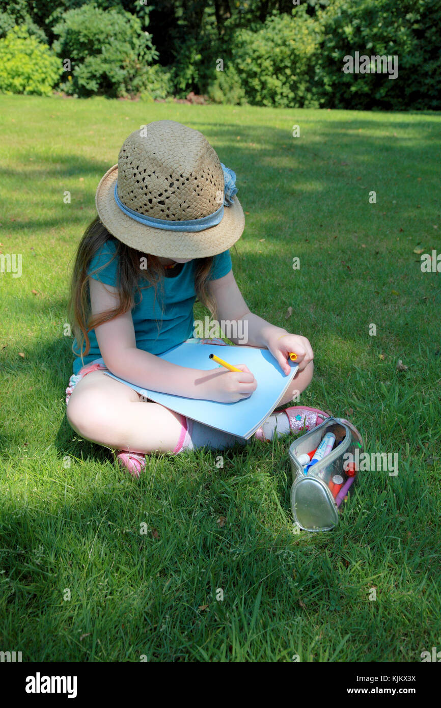 A little girl with a crayon and a sticker book in a garden on a summer's day - Stock Image