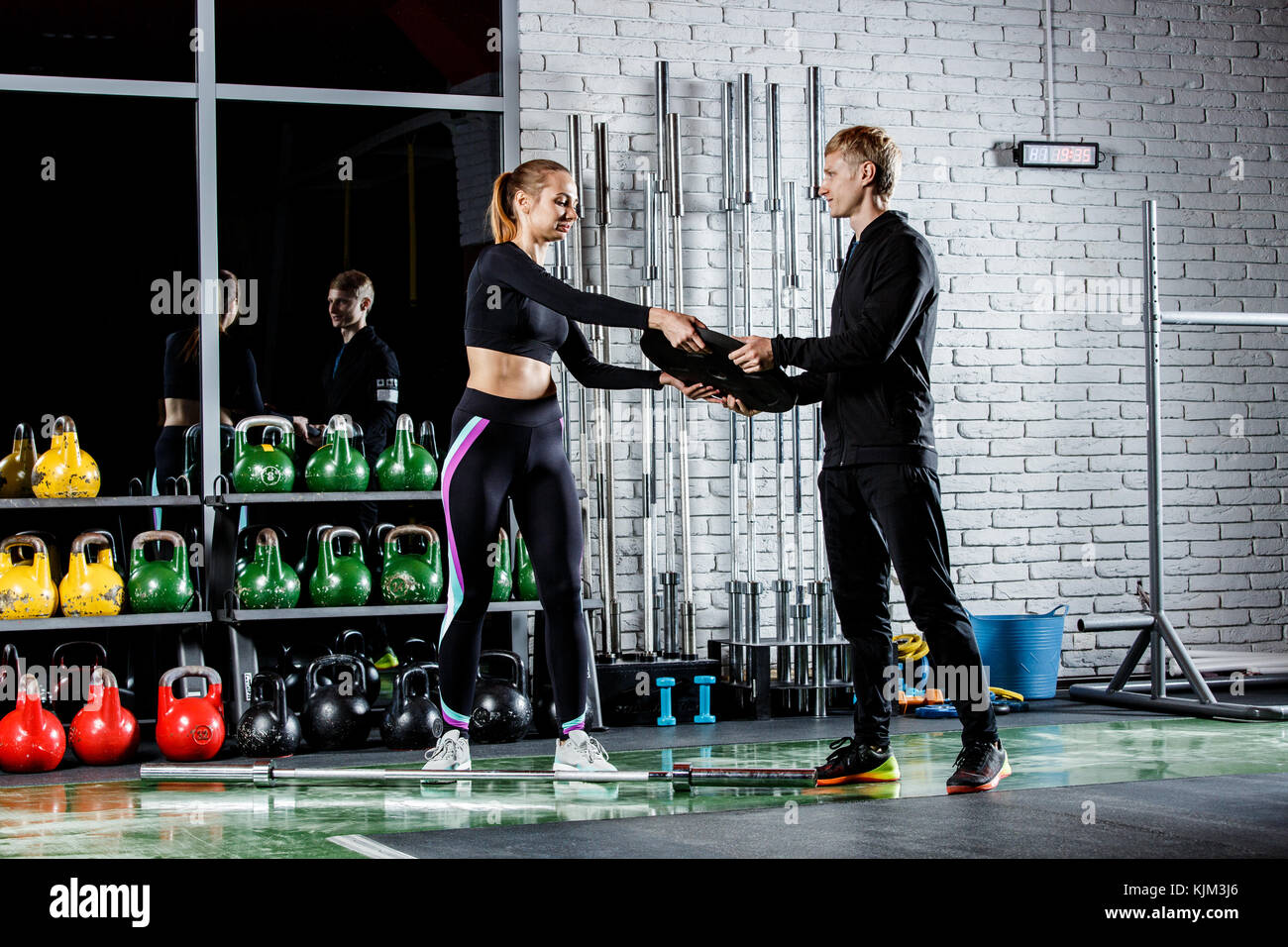 the coach gives a steel pancake to a young girl to perform exercises in the gym - Stock Image
