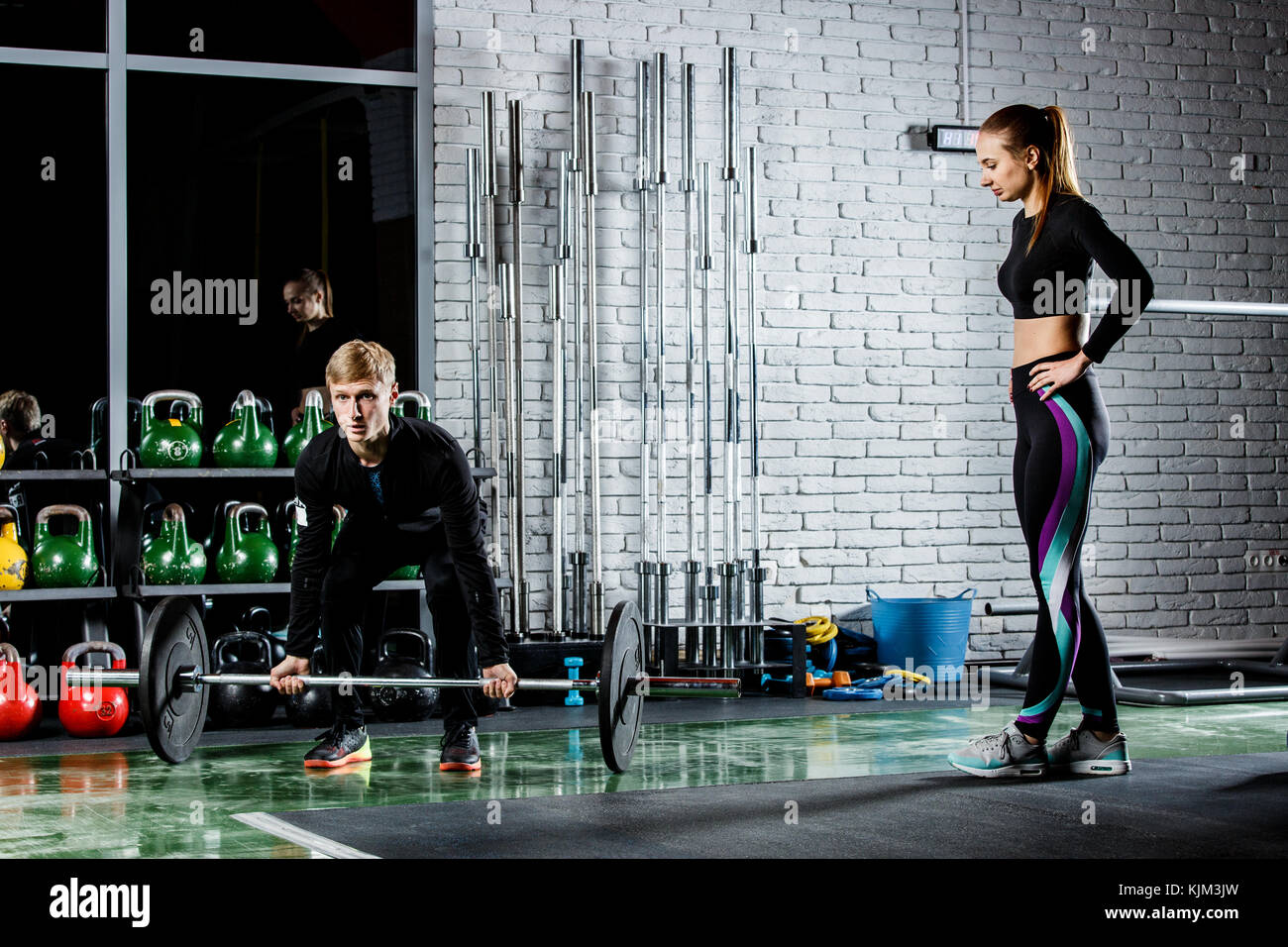 the coach show to the young girl how to perform the exercise with the stamp - Stock Image