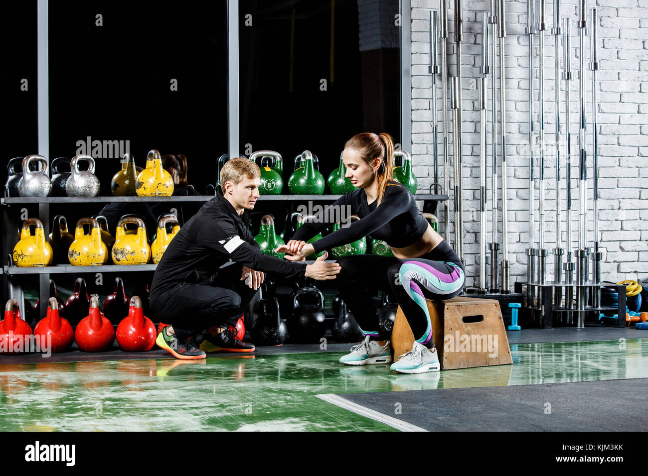 the young girl does the squat exercise in the gym with coach - Stock Image