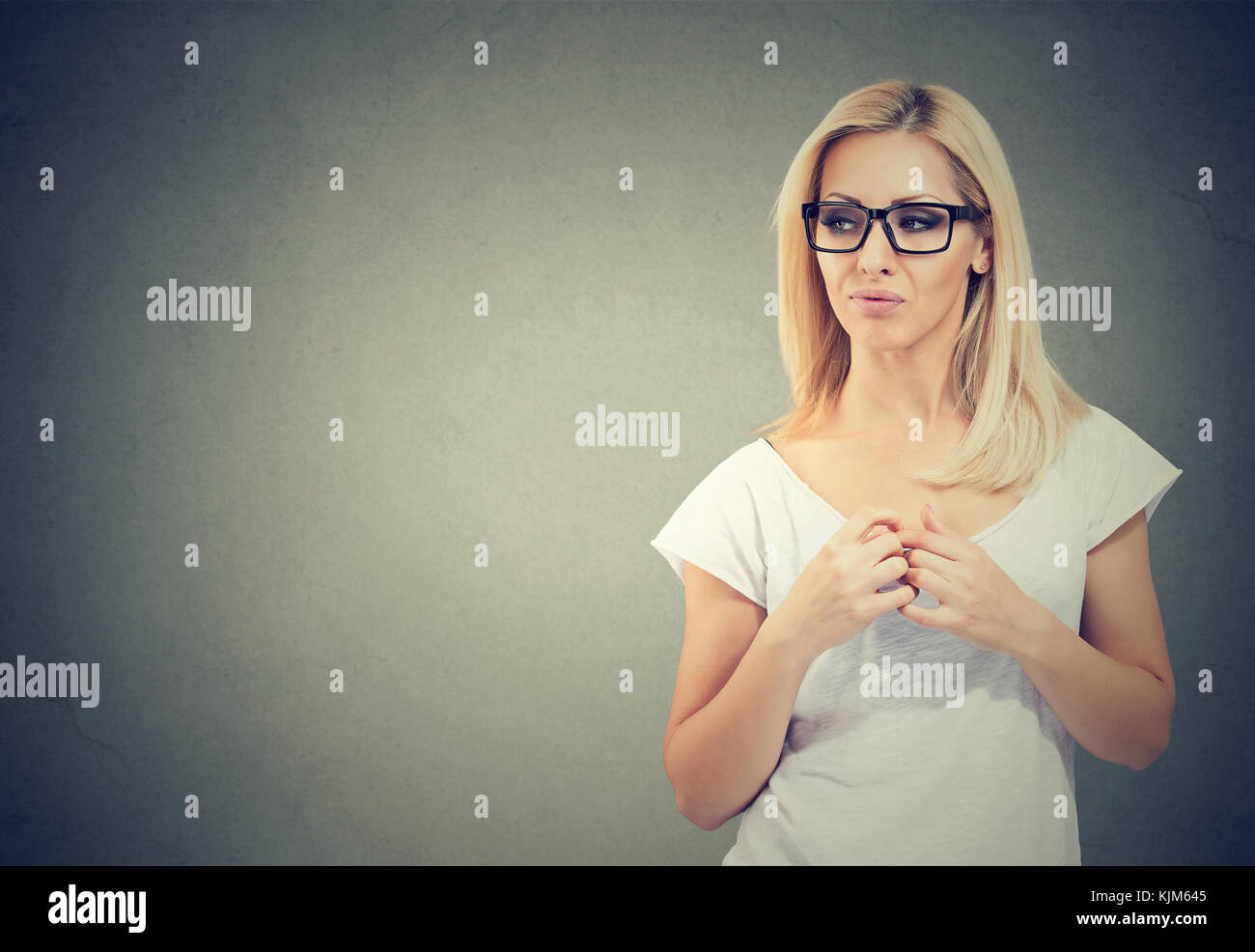 Displeased suspicious woman looking sideways isolated on gray background. Negative emotion perception - Stock Image