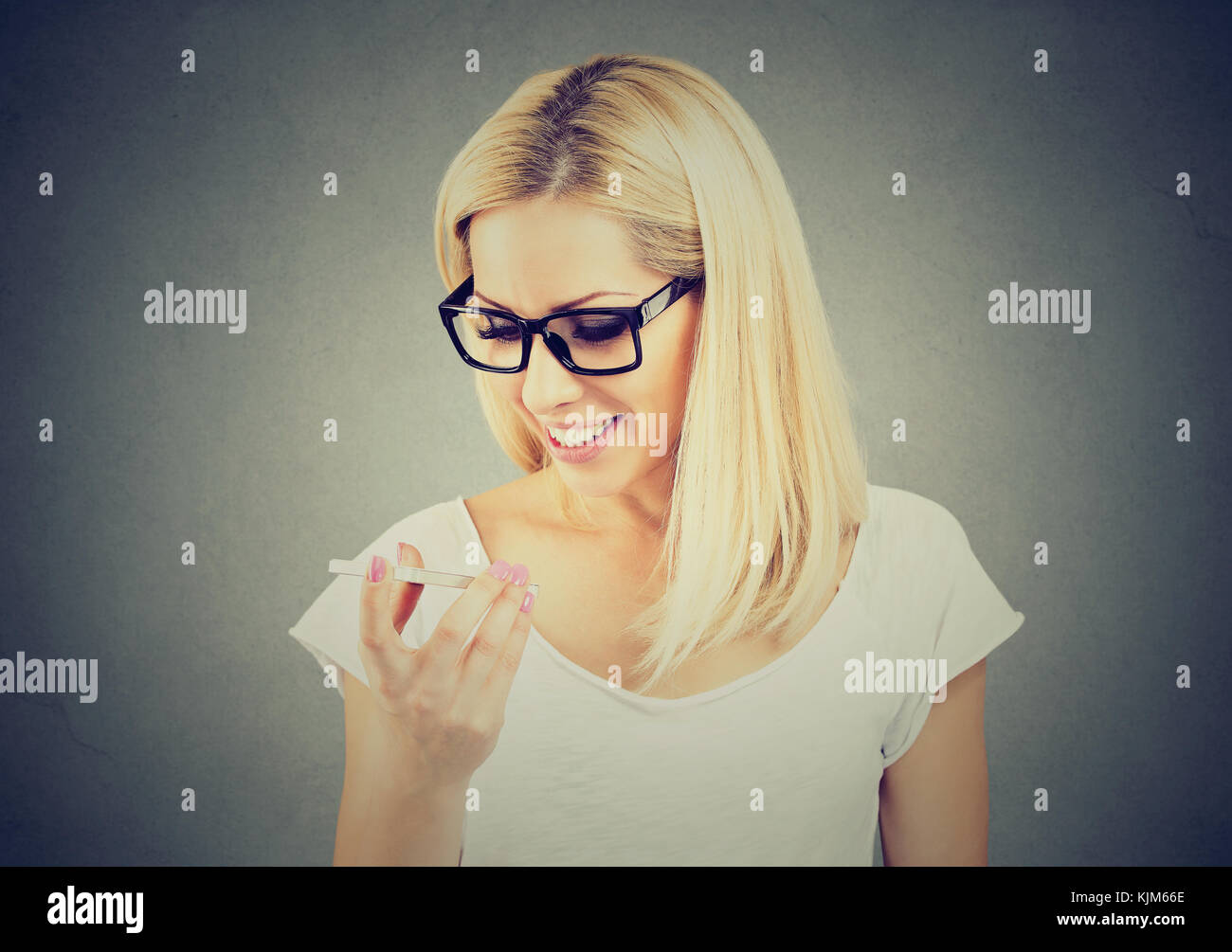 Woman wearing glasses using a smart phone voice recognition function online isolated on gray wall background - Stock Image