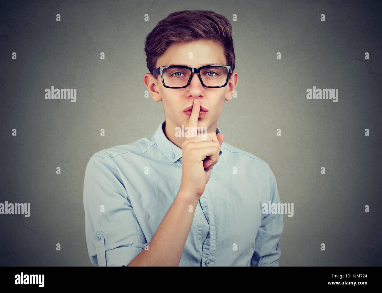 Secret guy. Man saying hush be quiet with finger on lips gesture looking at camera isolated on gray wall background. - Stock Image