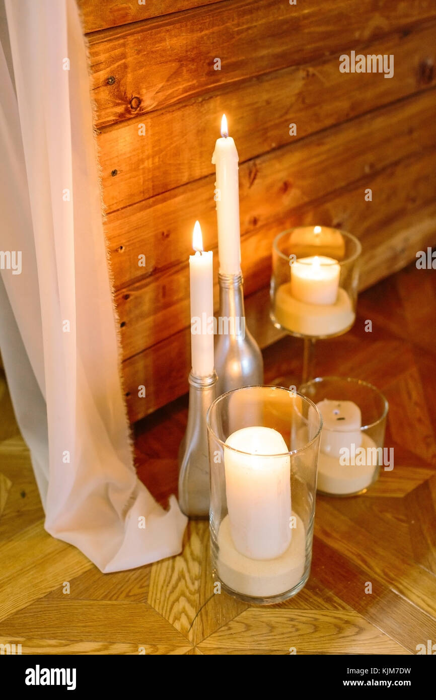 handmade, decor, cosiness concept. on the floorboards there are different design candle holders, few of them are - Stock Image