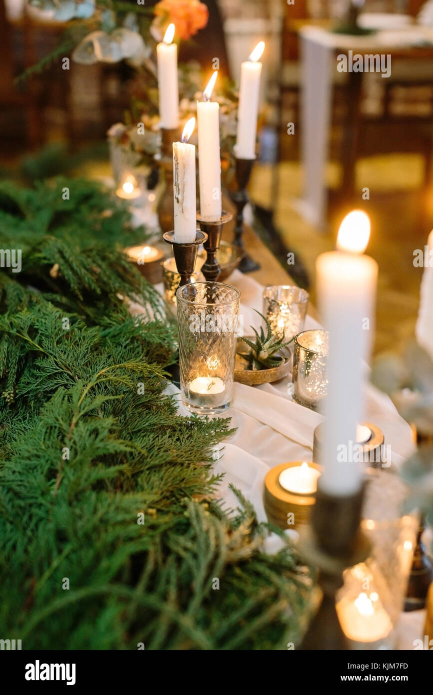 new year, interior design, winter concept. long table for celebrating decorated with numerous of shining candles - Stock Image